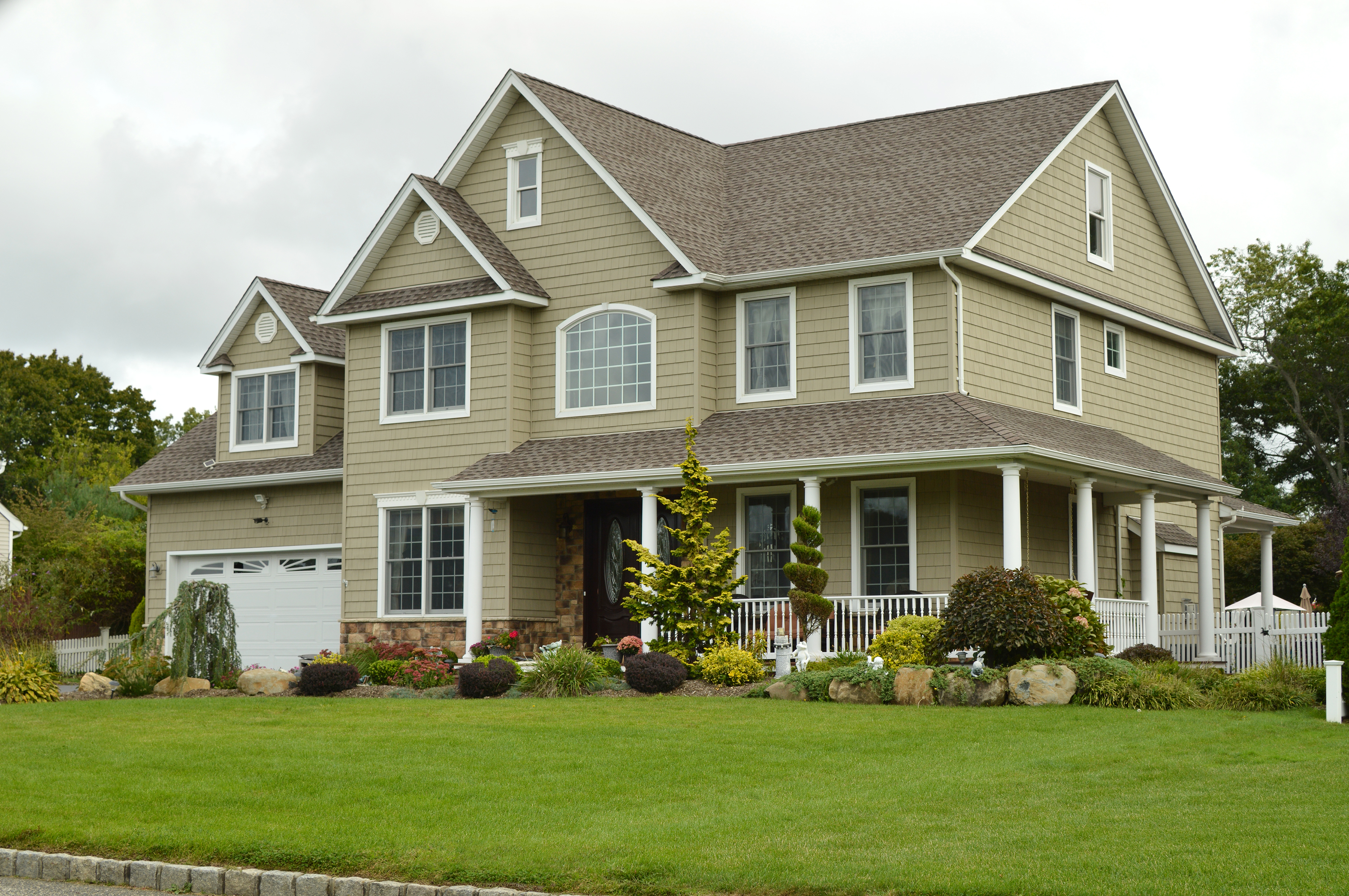 An olive two-story house with a covered patio and white garage sits on a bright green lawn.