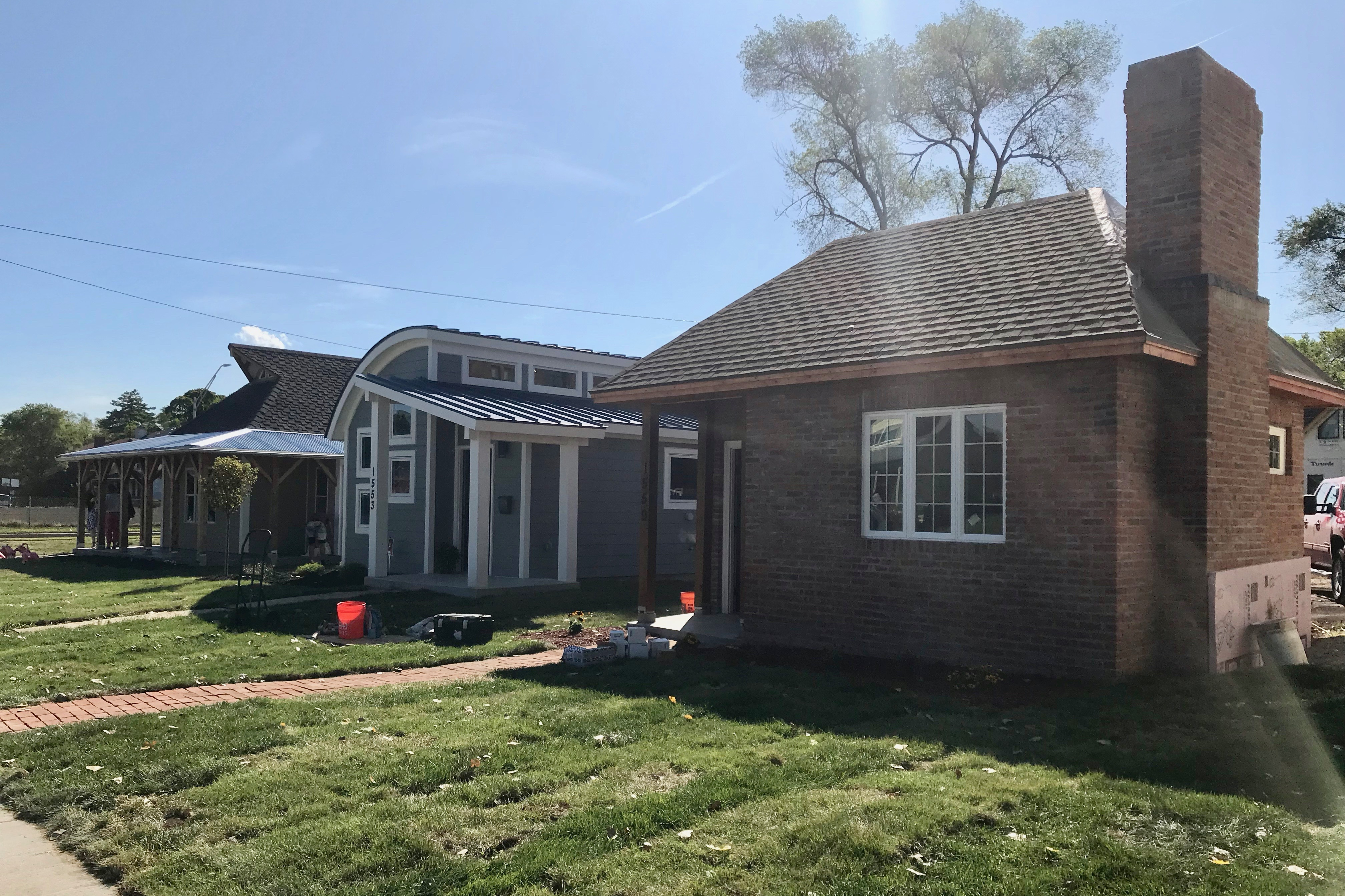 The sun is shining on three tiny homes in three different styles: one brick, another with a sloped roof, and the last one with a low-pitched overhang. All three have well-cut front lawns.