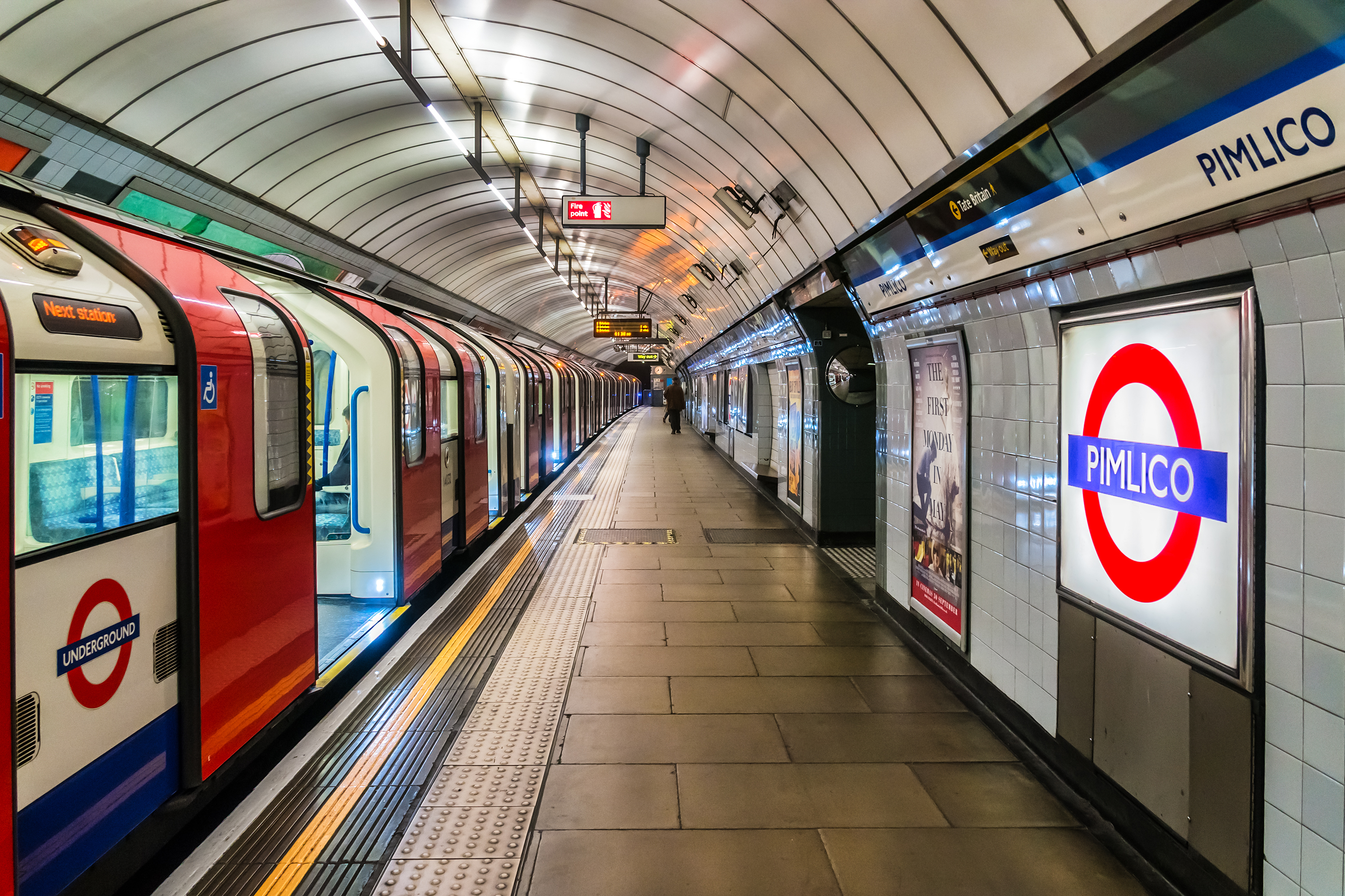 A London subway platform with a train stopped on the track to the left.