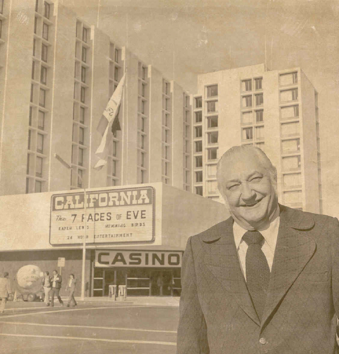A man stands in front of a hotel in a sepia-tone photo