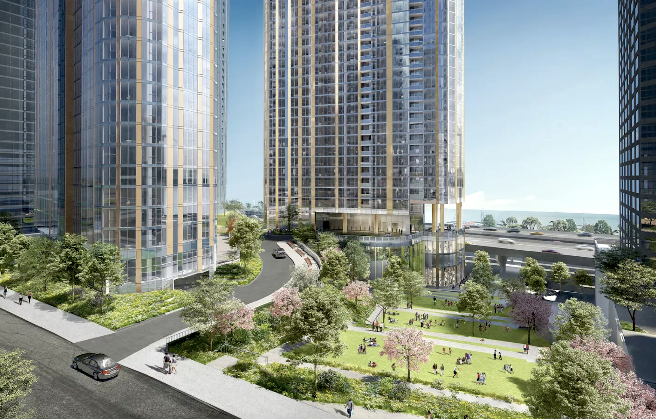 Two high-rise towers with glass and metal exteriors rise next to a sloping downward park and path below an elevated highway. A large body of water is on the horizon.