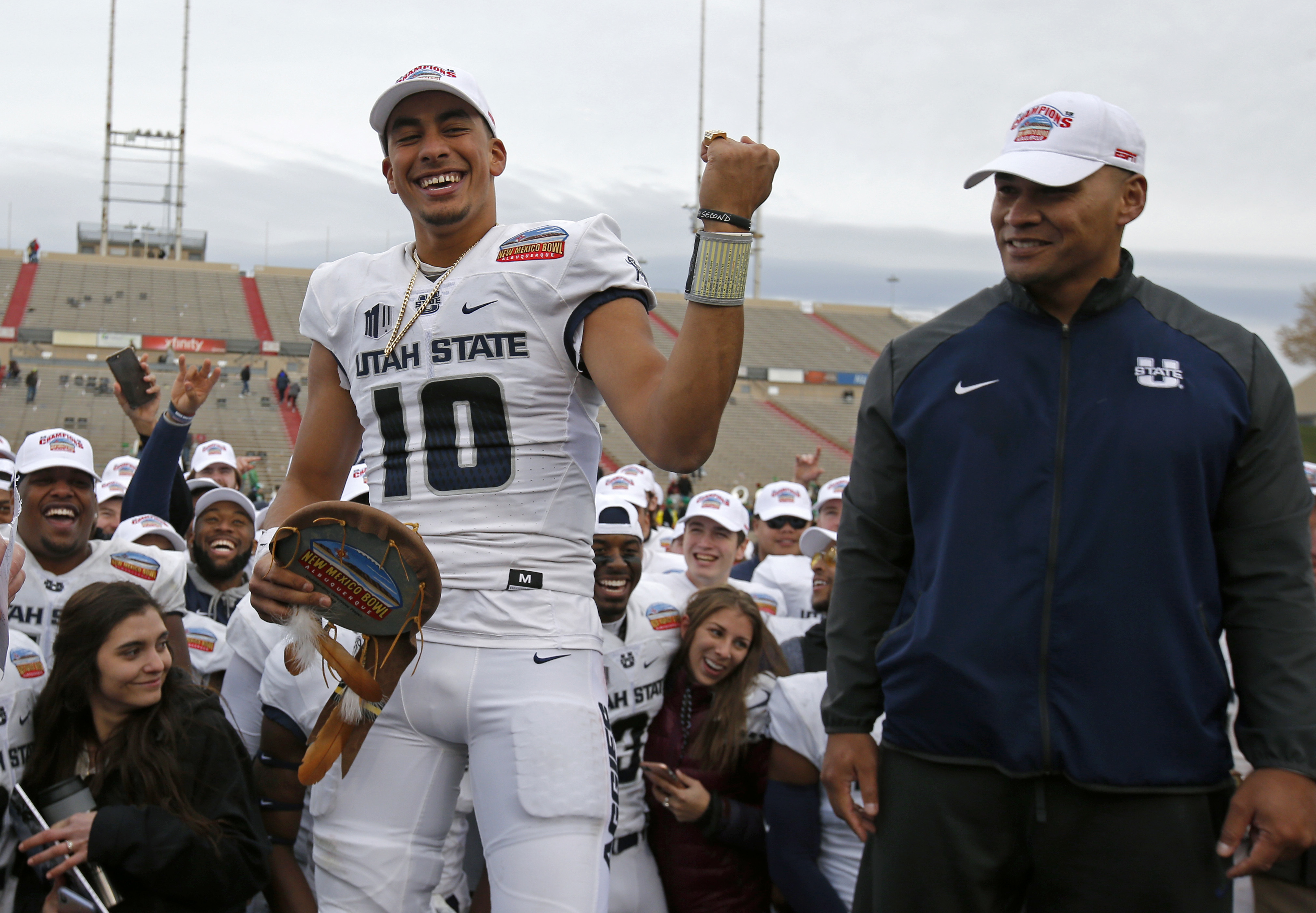 Utah State quarterback Jordan Love (10) celebrates after being named the Outstanding Offensive Player as interim head coach Frank Maile looks on, following the New Mexico Bowl NCAA college football game in Albuquerque, N.M., Saturday, Dec. 15, 2018. Utah