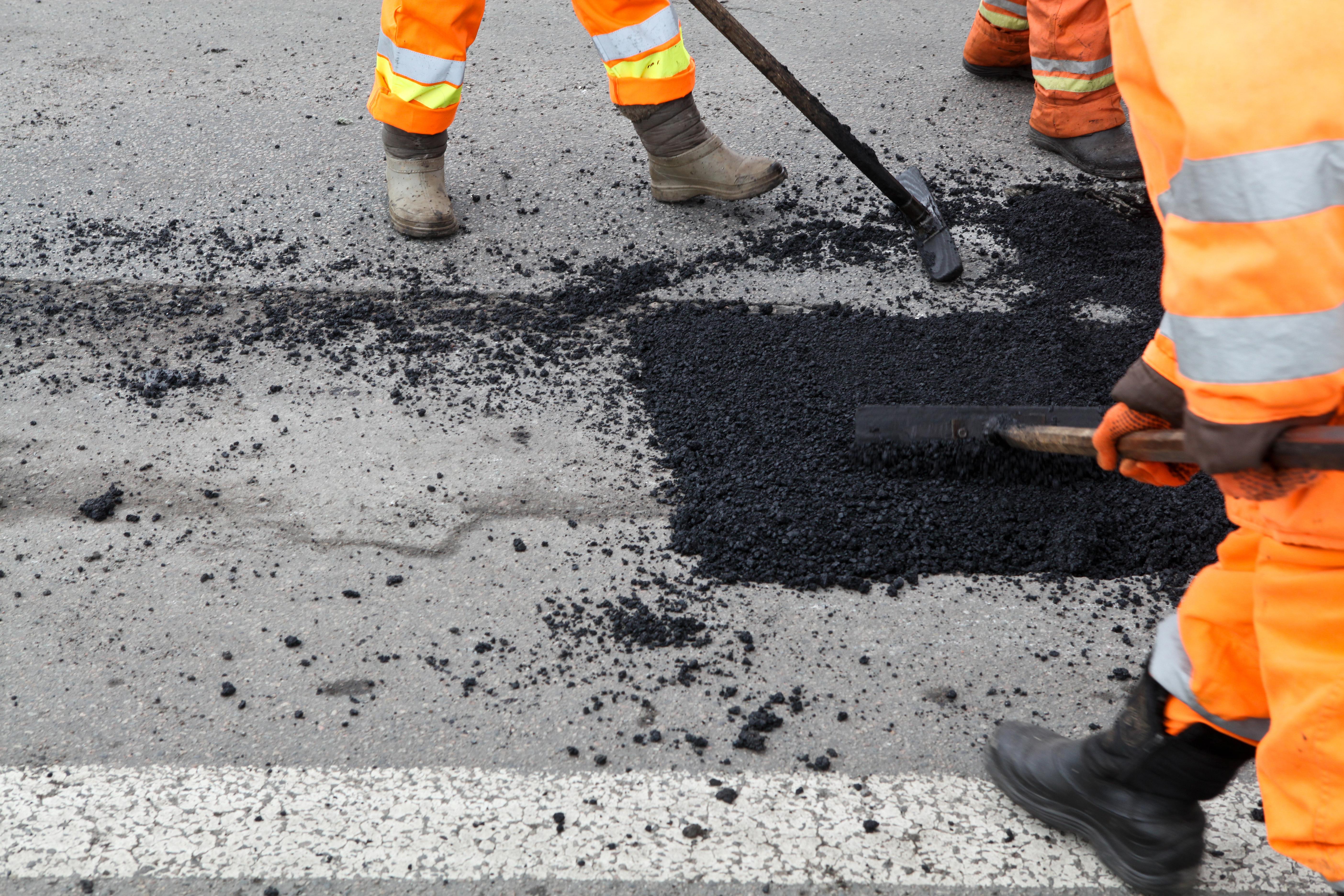 Workers in orange work suits repaving a street.