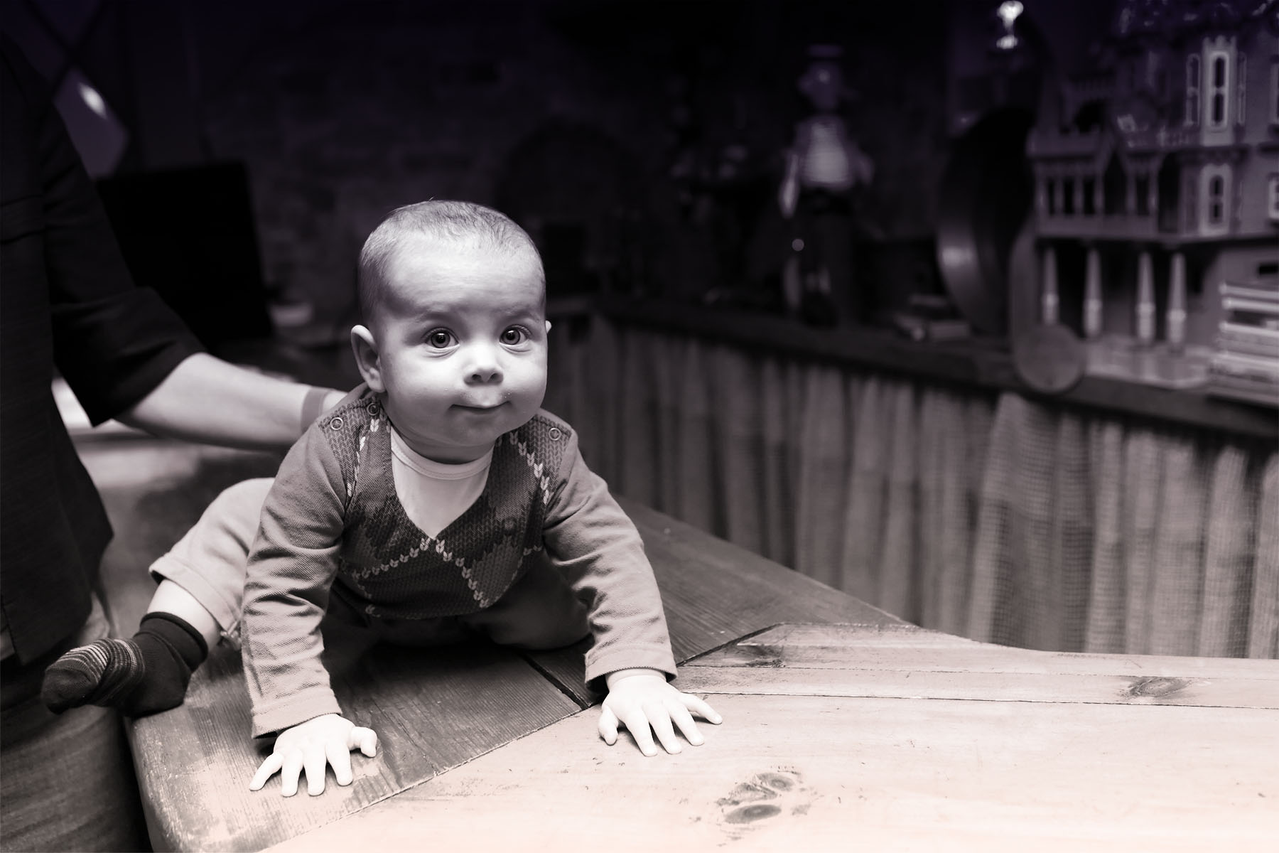 A black and white photo of a white baby in a long sleeve shirt, pants, and socks sitting on top of a wooden bar with hands stretched out and a parent's arm behind them.