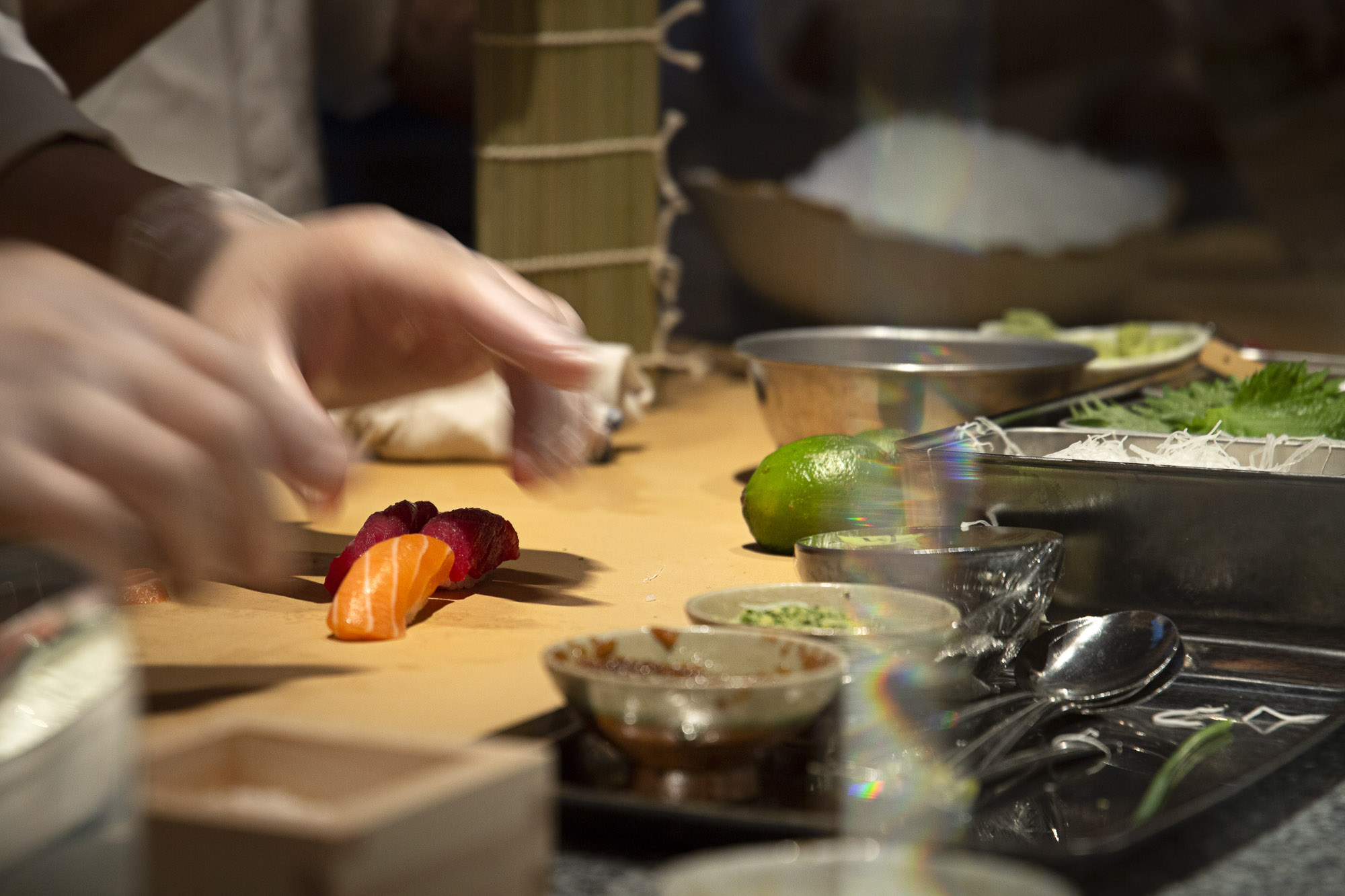 Hands reach towards a piece of sushi set on a cutting board surrounded by dishes of indiscernible ingredients