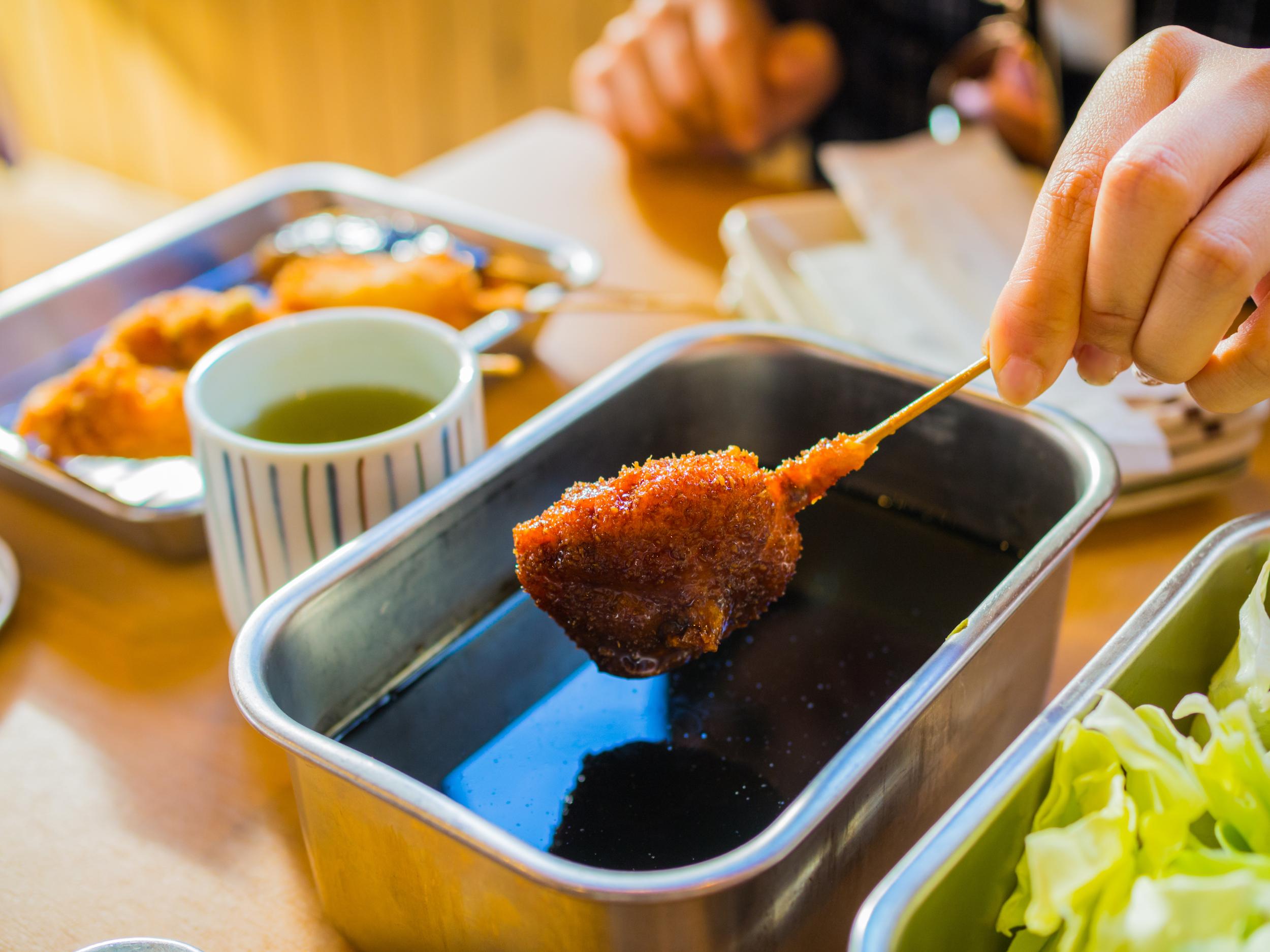 Kushikatsu, a deep-fried Japanese skewer, with sauce