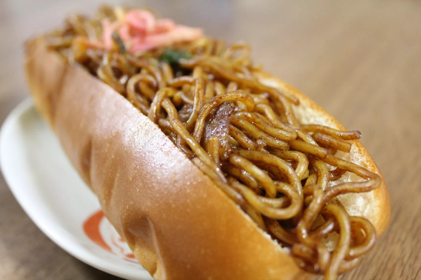 A hot dog bun stuffed with yellow fried wheat noodles and topped with a little bit of pink pickled ginger and green seaweed powder.