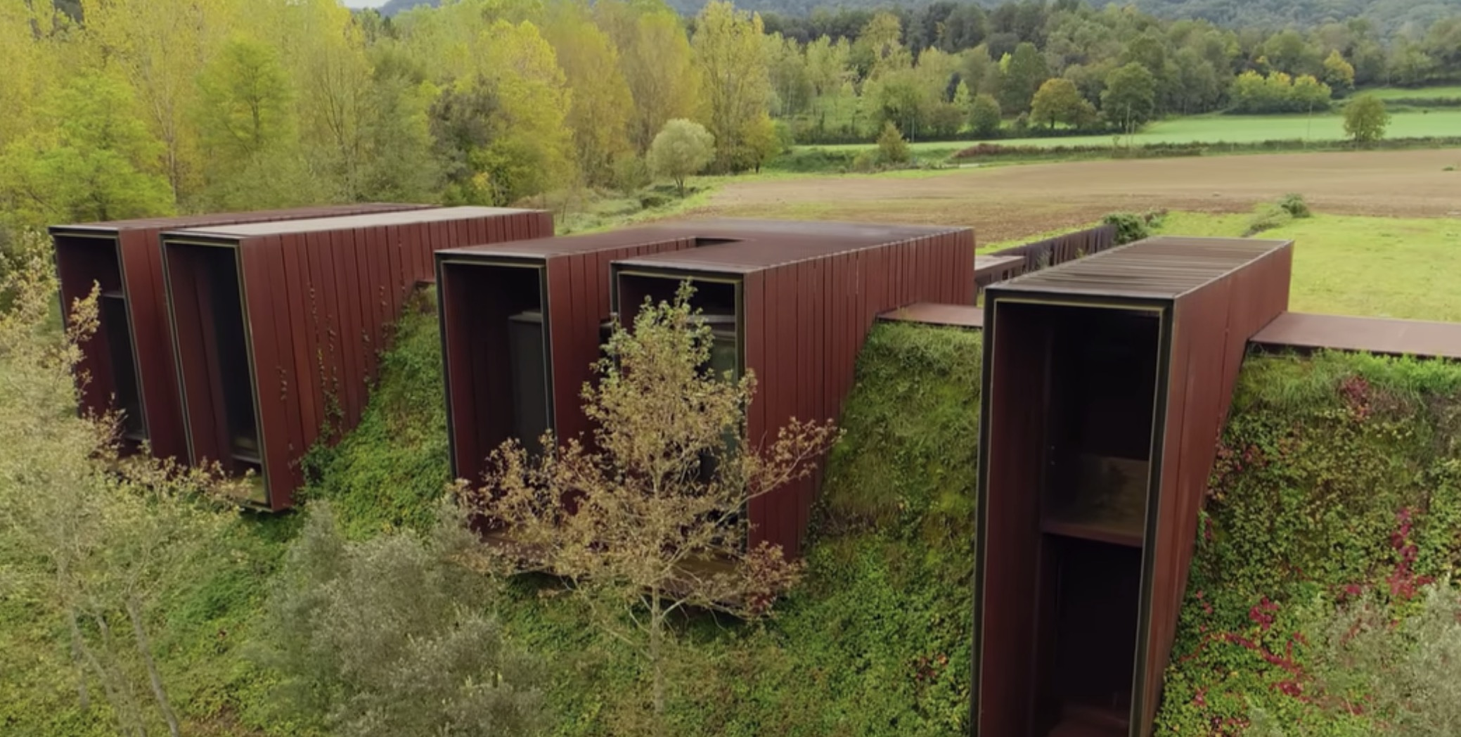 A bermed house built into a green hill features five agrarian-inspired boxes meant to look like farm sheds.