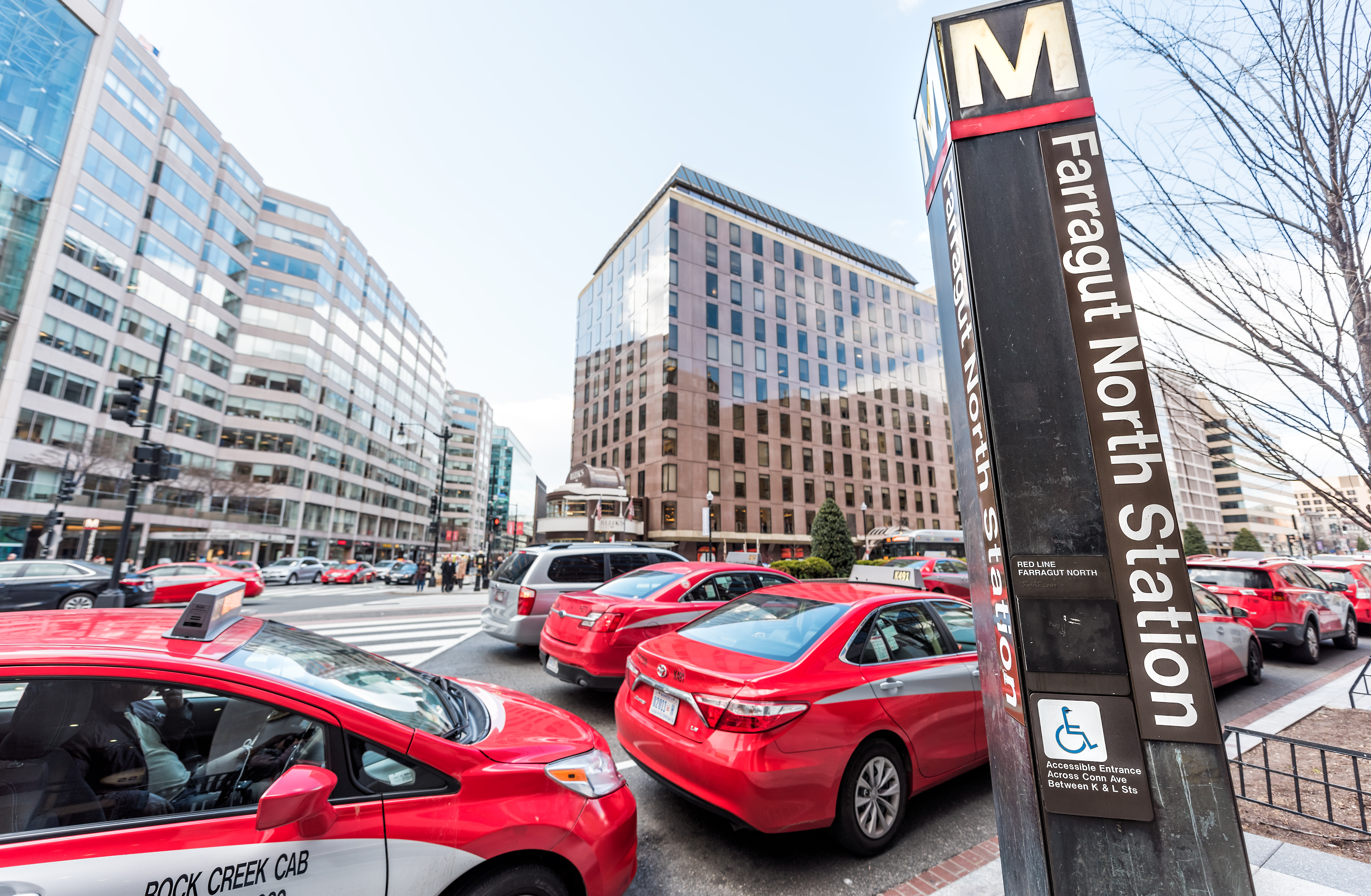A sign for the Farragut North station on Metro's Red Line. There are several red taxis and office buildings in the background.