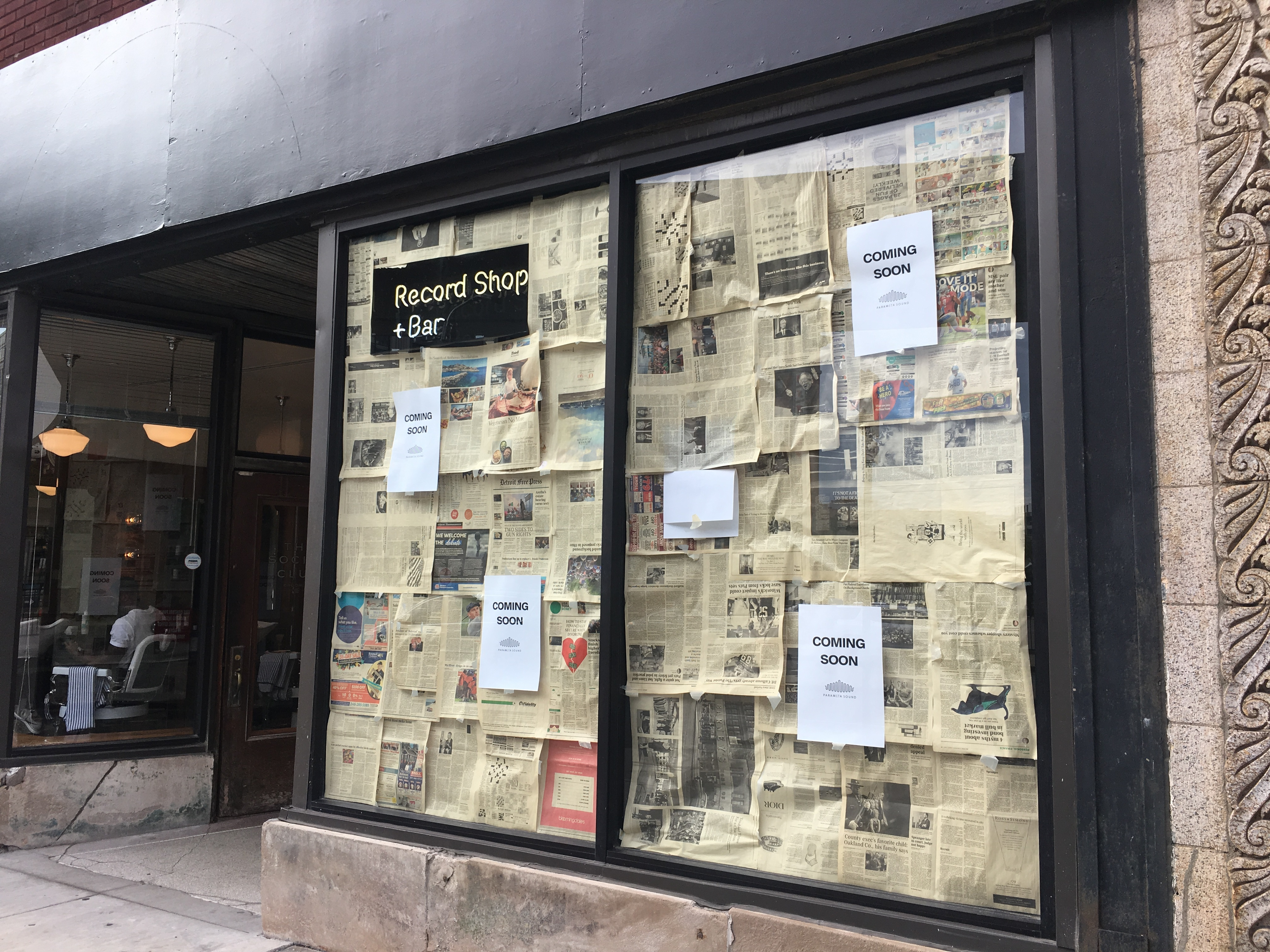 """Papered over windows at Paramita Sound feature printed signs reading """"coming soon"""" with a neon sign that says Record Shop + Bar."""