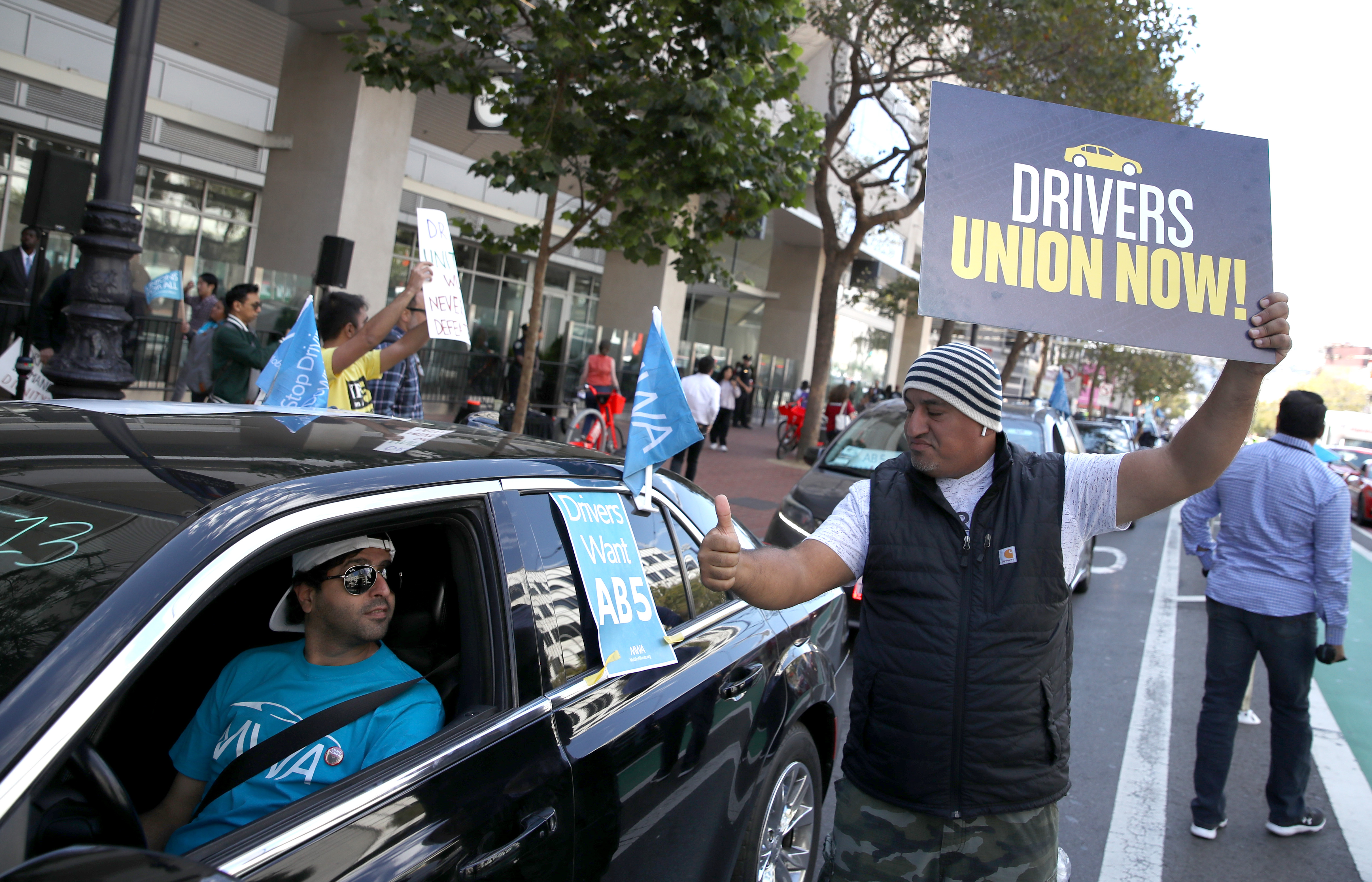 """Uber drivers hold signs reading """"Drivers union now!"""" on the street outside of Uber's headquarters on August 27, 2019, in San Francisco, California."""