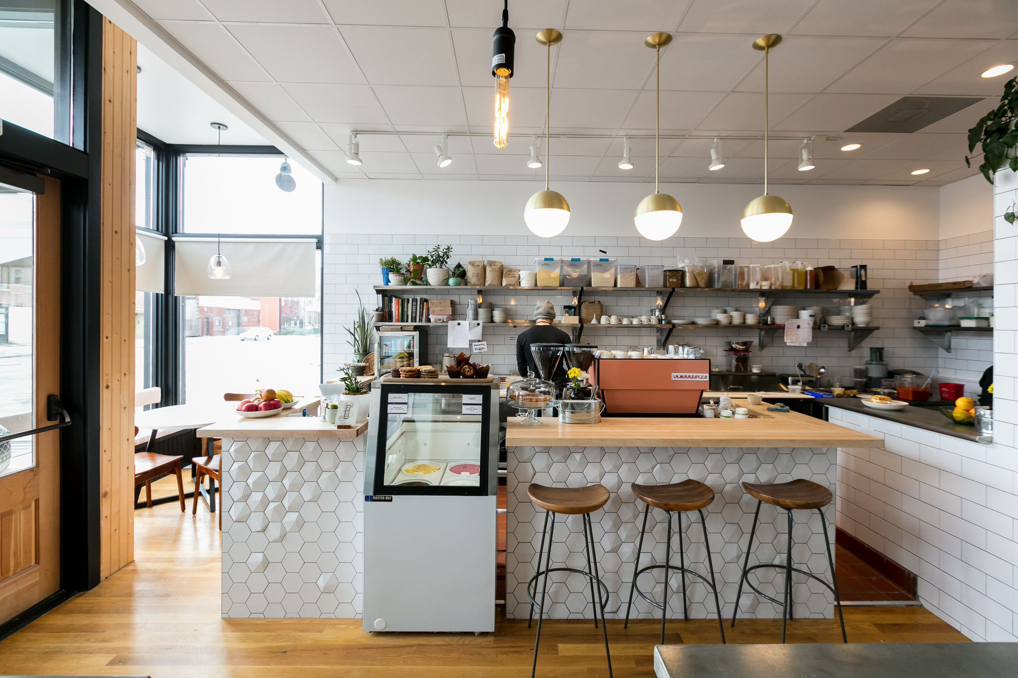 The counter at Folk has white honeycomb tiles with butcher block.