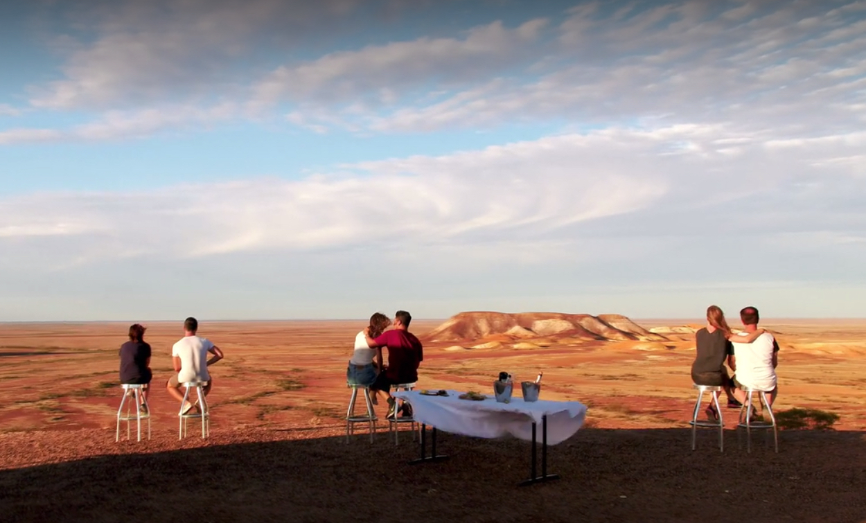 Three pairs of people sit in front of panoramic views of a rocky landscape in the distance. A table with snacks and refreshments is nearby.