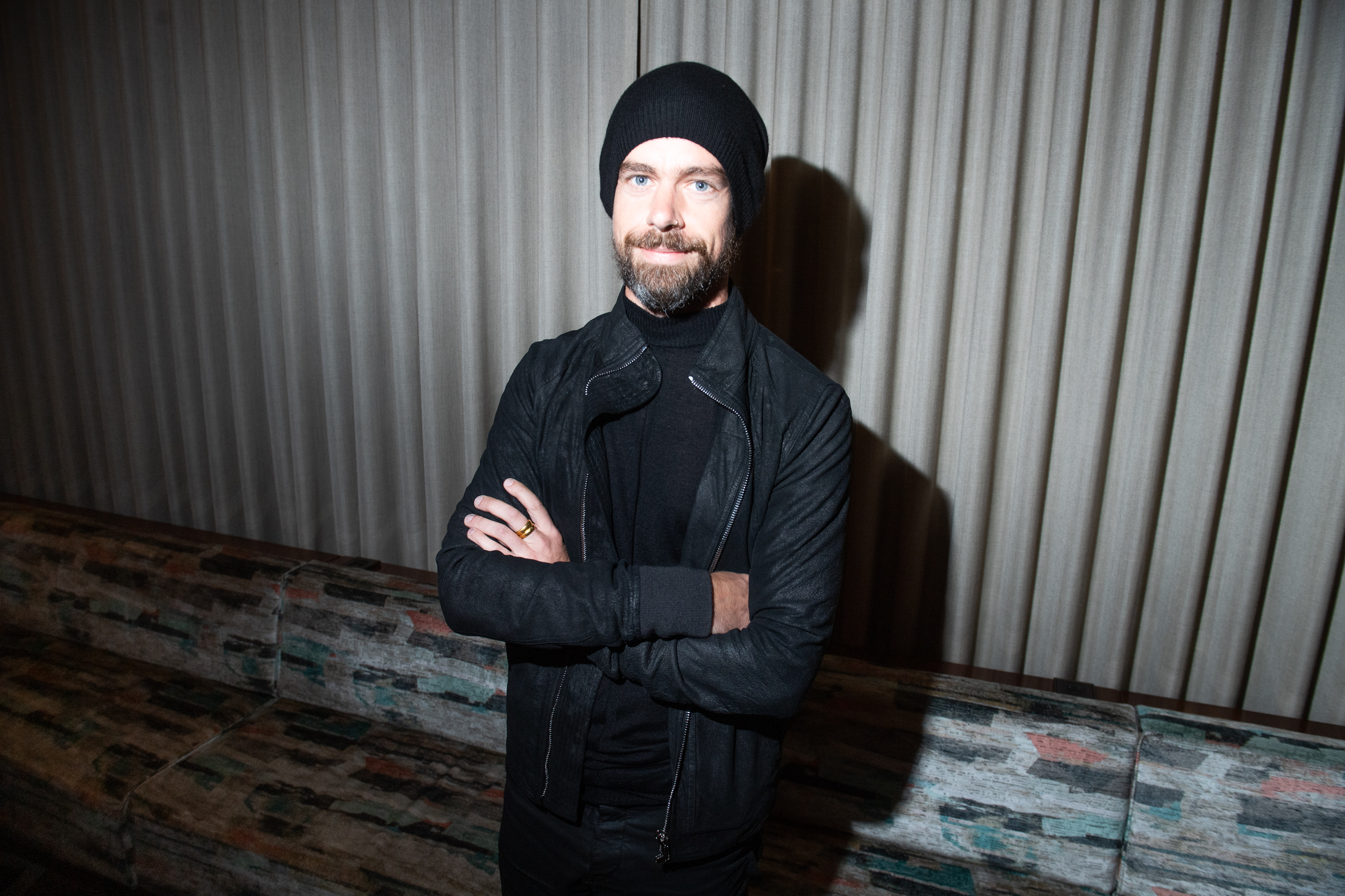 Twitter CEO Jack Dorsey standing in front of an exterior wall with his arms folded.