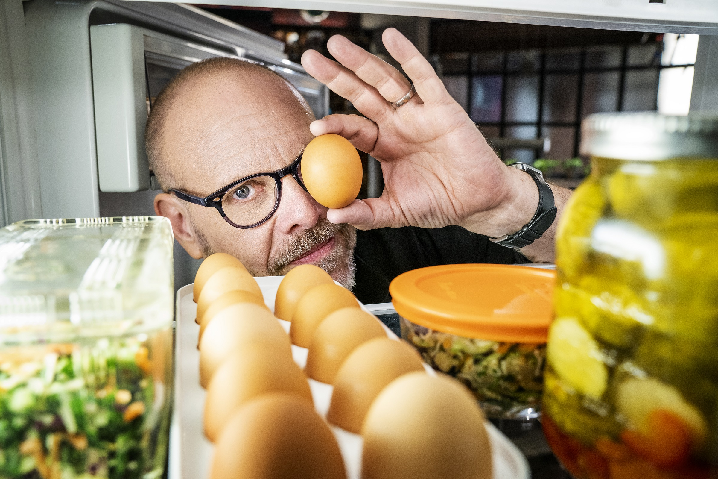 """Alton Brown, as seen from inside a well-stocked refrigerator on """"Good Eats: The Return,"""" holds an egg in front of one eye."""