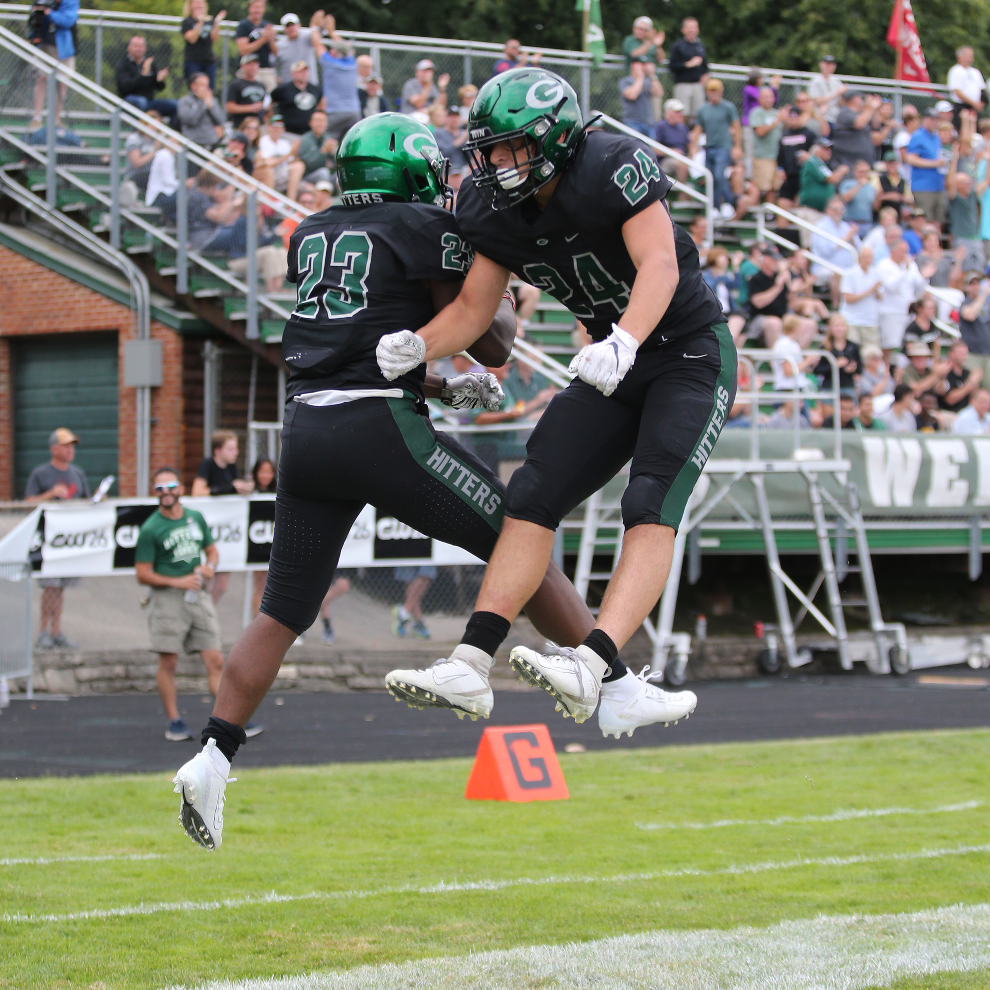Glenbard West's Jalen Moore (23) and Nic Seifert (24) celebrate one of Moore's touchdowns.