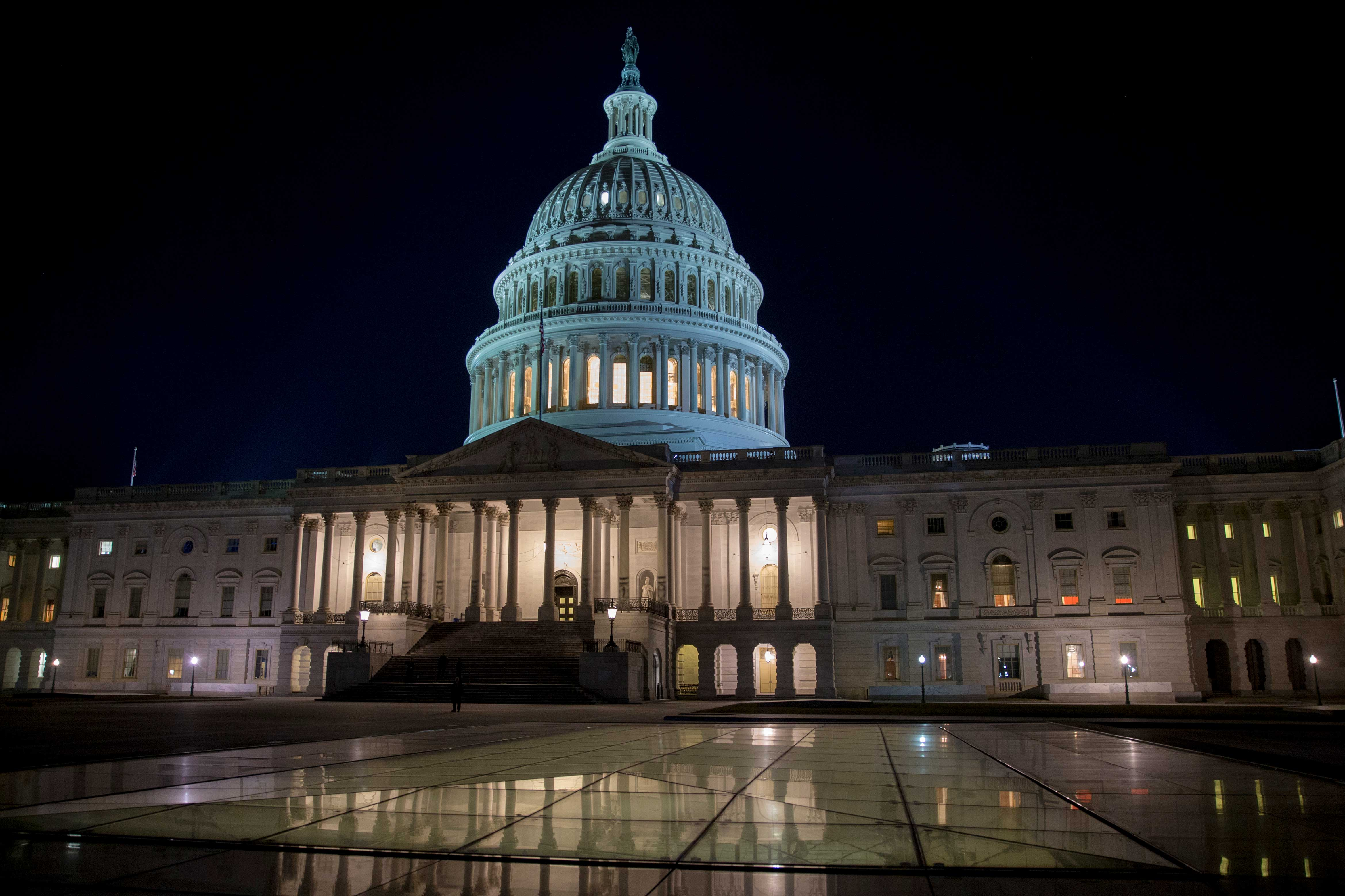 The exterior of the US Capitol building at night with its lights on.