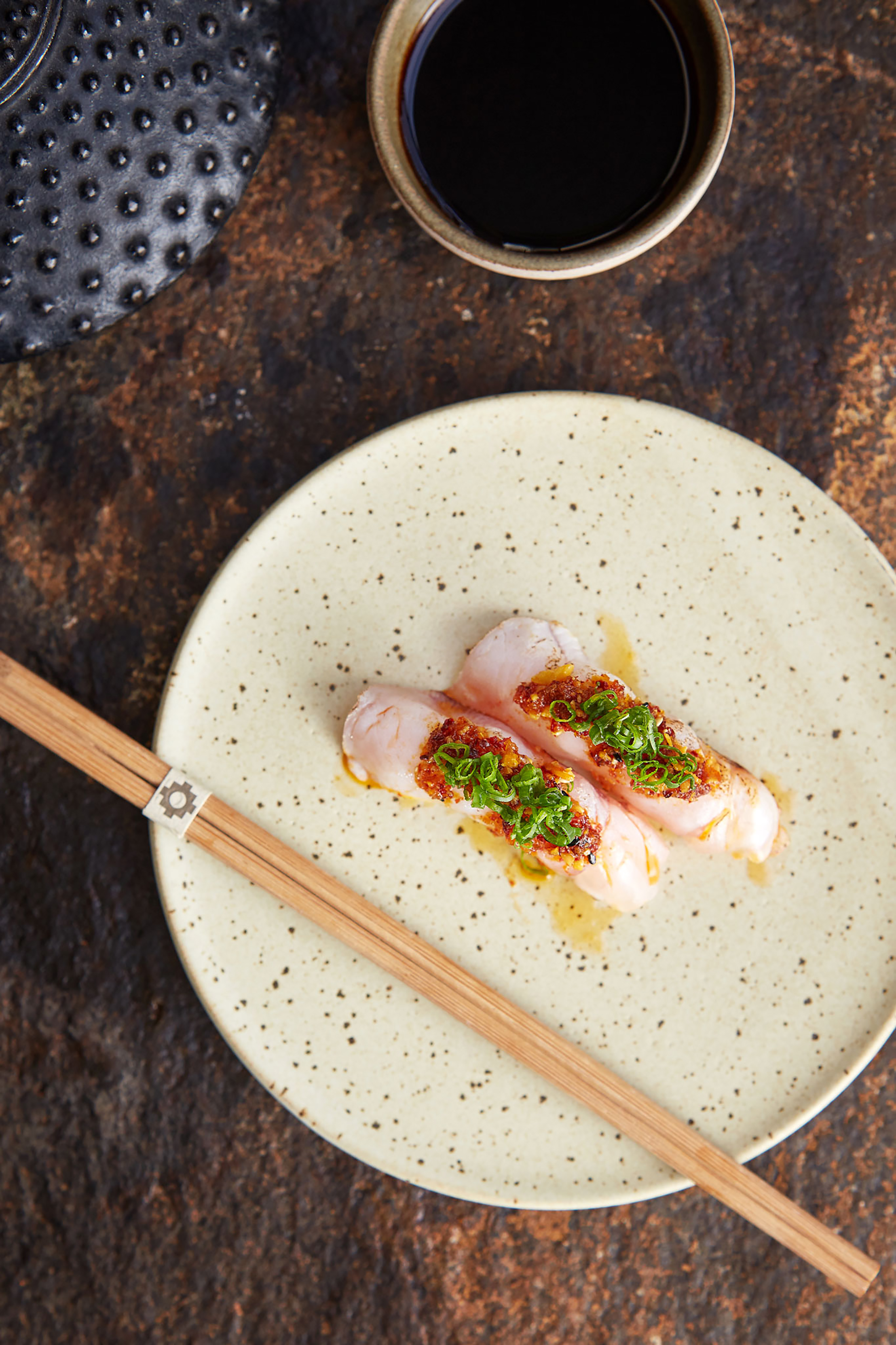Overhead shot of spicy hamachi on a white plate with chopsticks on the side of the plate