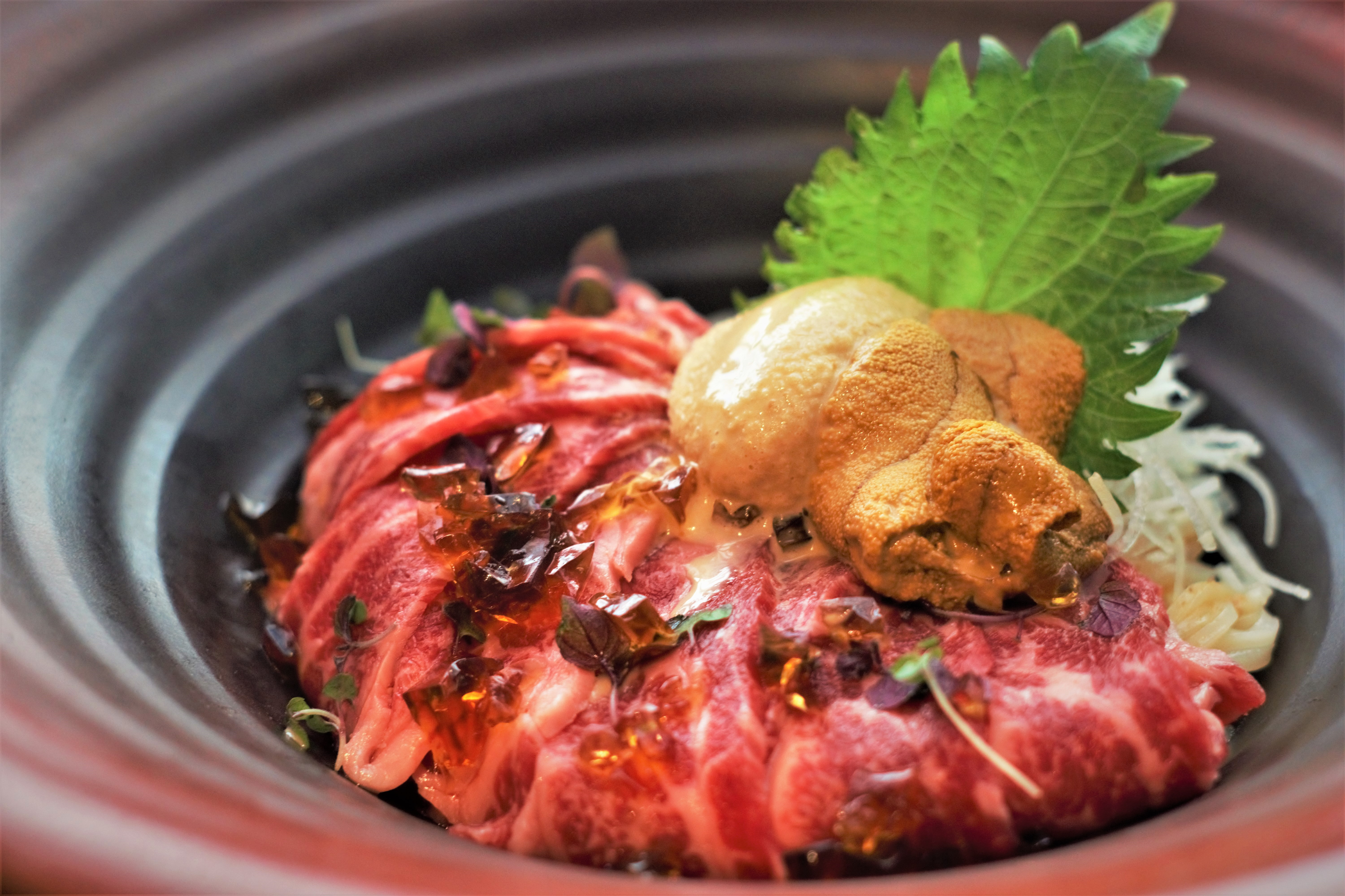 This exclusive dish from the Boston location of Tsurutontan features thin, rare strips of wagyu with udon noodles peeking out underneath and a big dollop of orange uni on top.