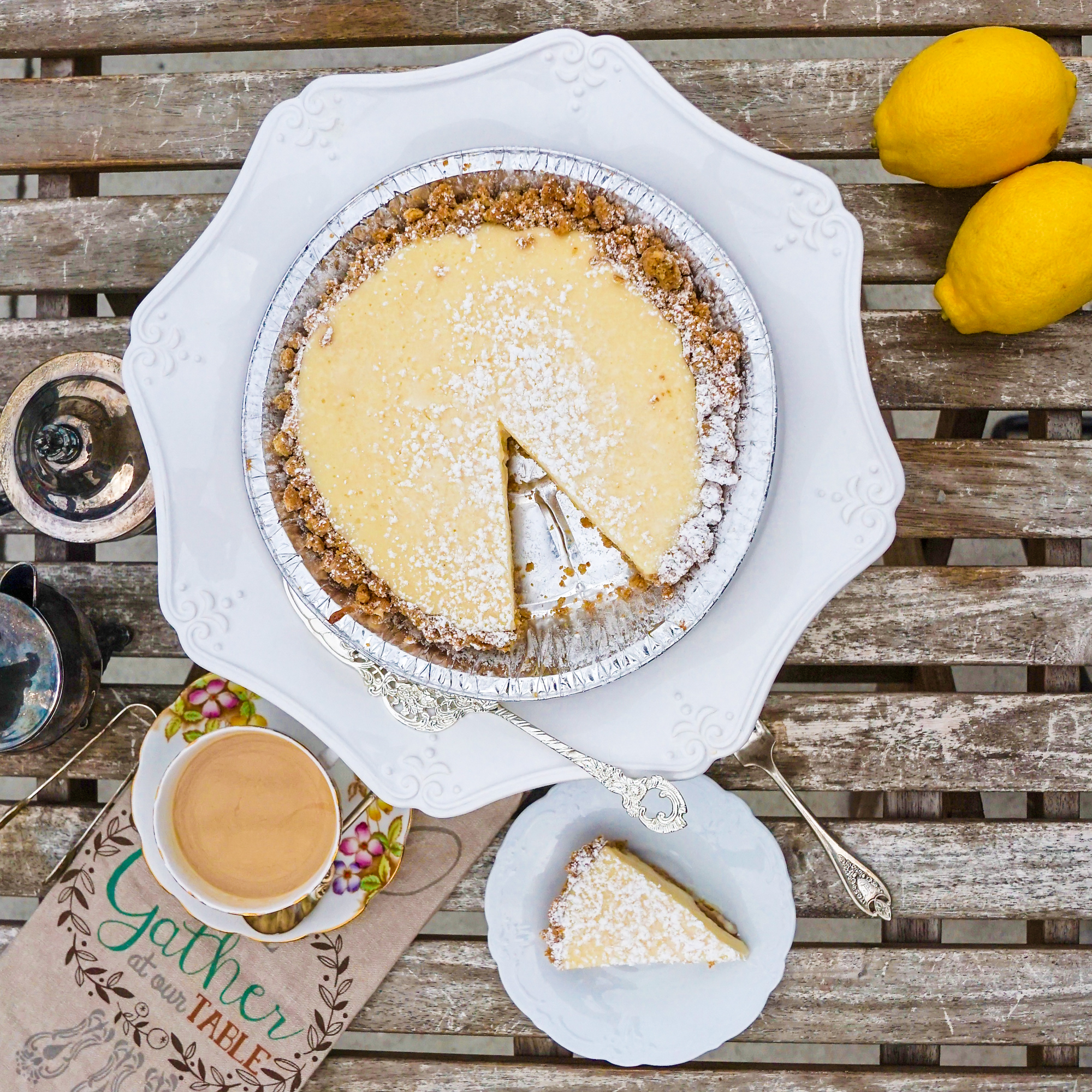 A pie in a metal tin with a cookie crust and a creamy yellow filling with one slice removed. It's dusted with powdered sugar.
