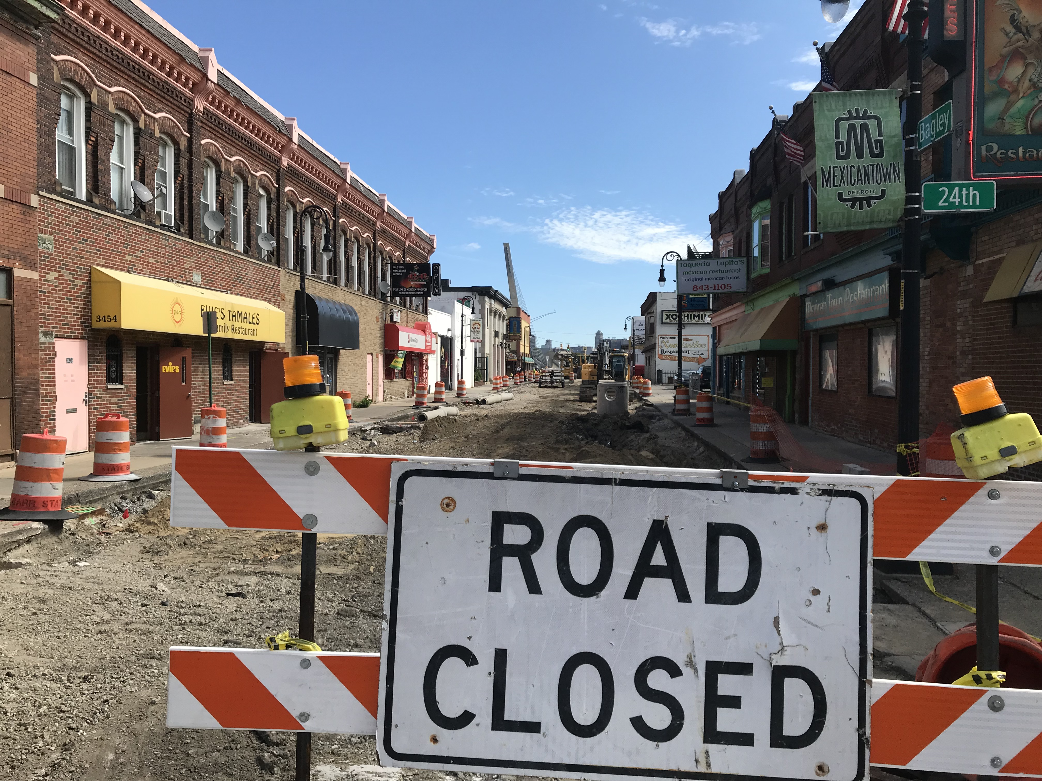 "A ""Road Closed"" sign in front of a road with the street torn up. Businesses in brick buildings line either side of the street."
