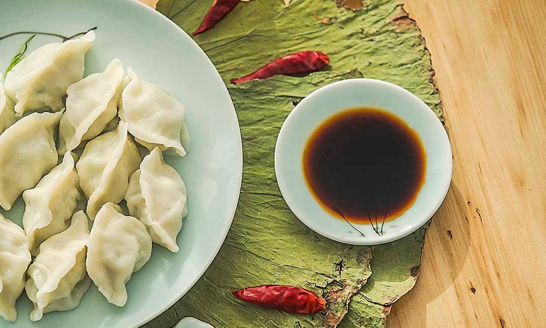 A plate of Chinese dumplings and a dish of dipping sauce.