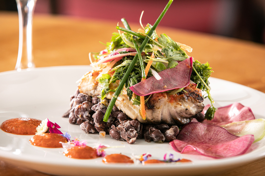 A white plate contains a piece of roasted fish on top of black beans, topped with a green salad. It's decorated with small flowers and thin slices of pink radish.