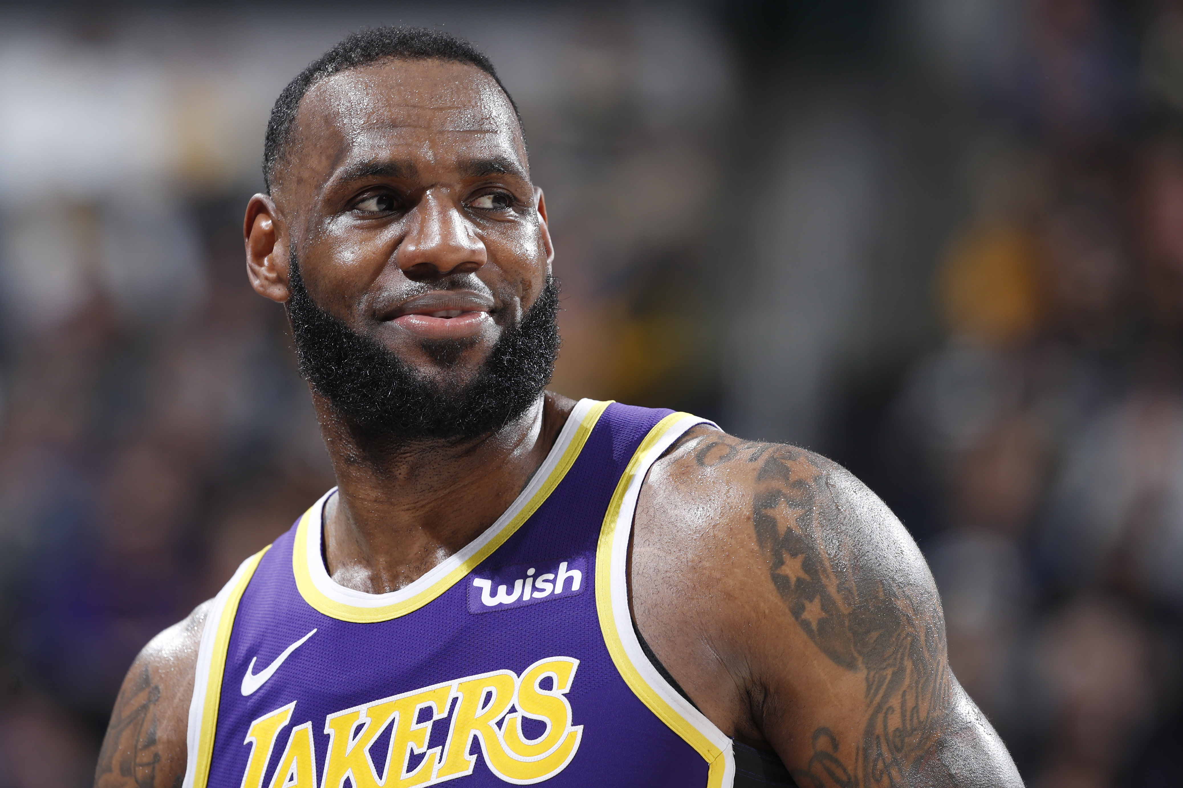 In a purple Lakers jersey with gold lettering, LeBron James sweats and smiles on the court with fans blurred in the background.