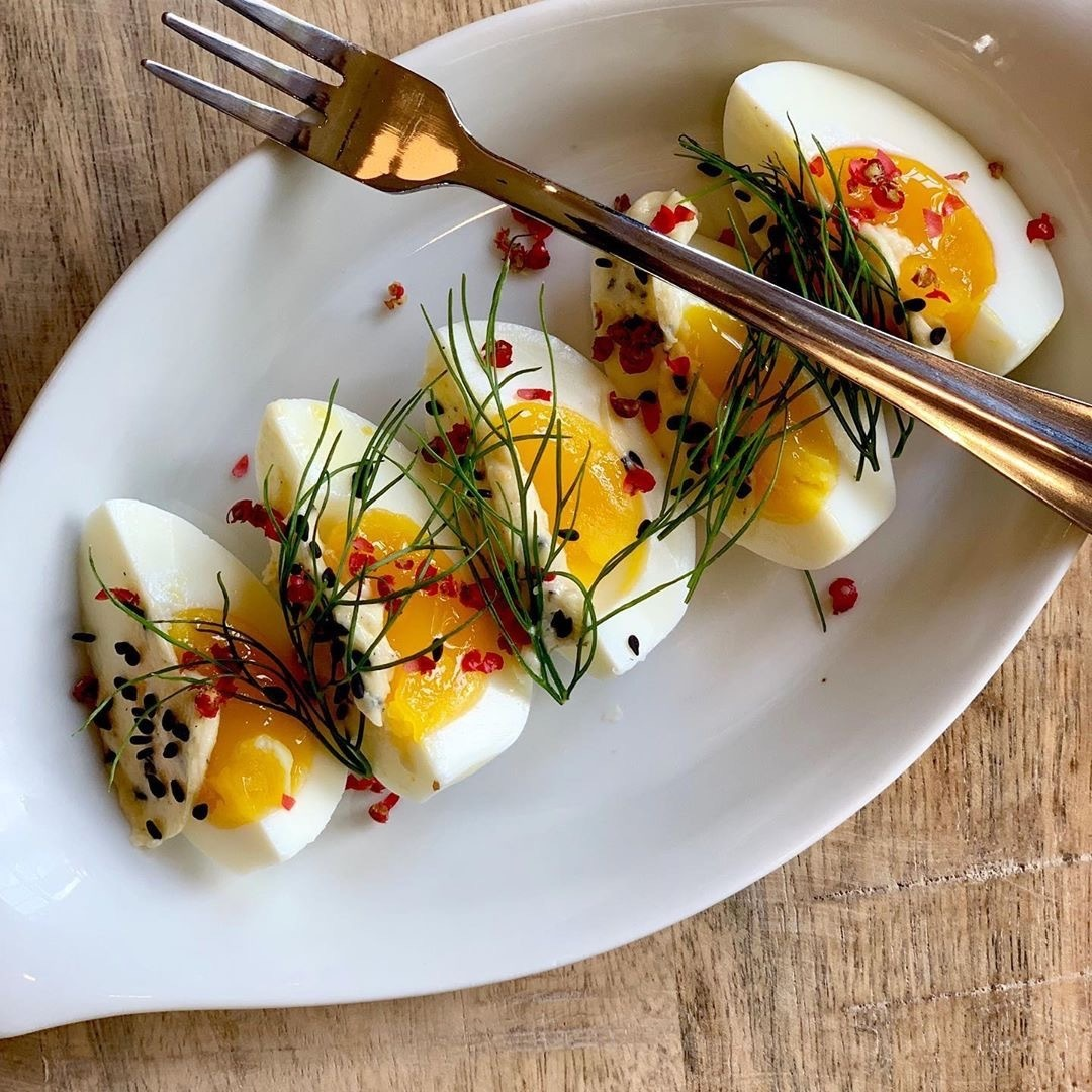 Soft egg, black sesame-miso butter, pink peppercorn on a white plate with a fork