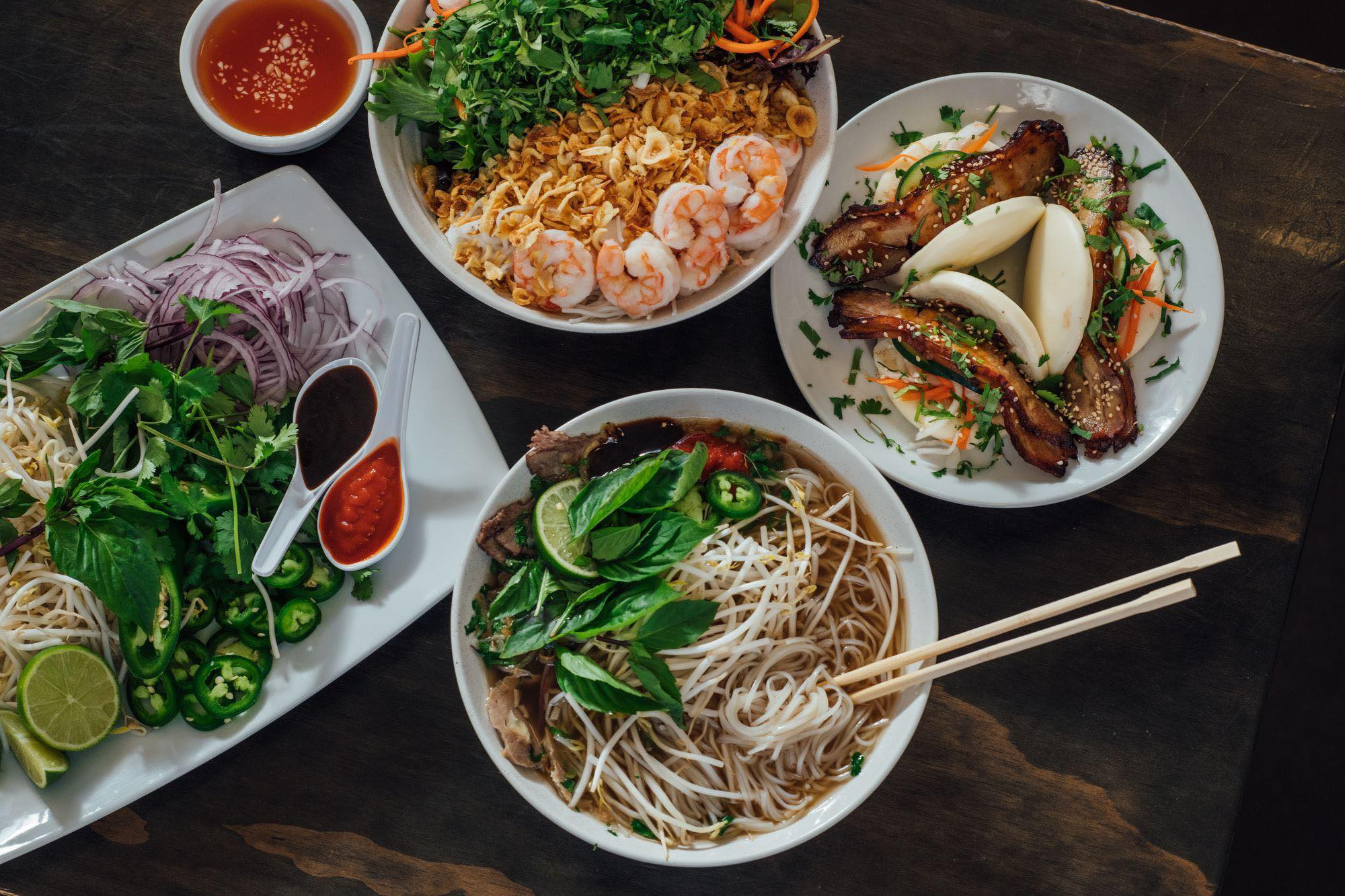 A bowl of pho, a plate of red onion, jalapeno, cilantro, and bean sprouts, a plate of pork belly steamed buns, and a bowl of vermicelli noodles topped with shrimp.