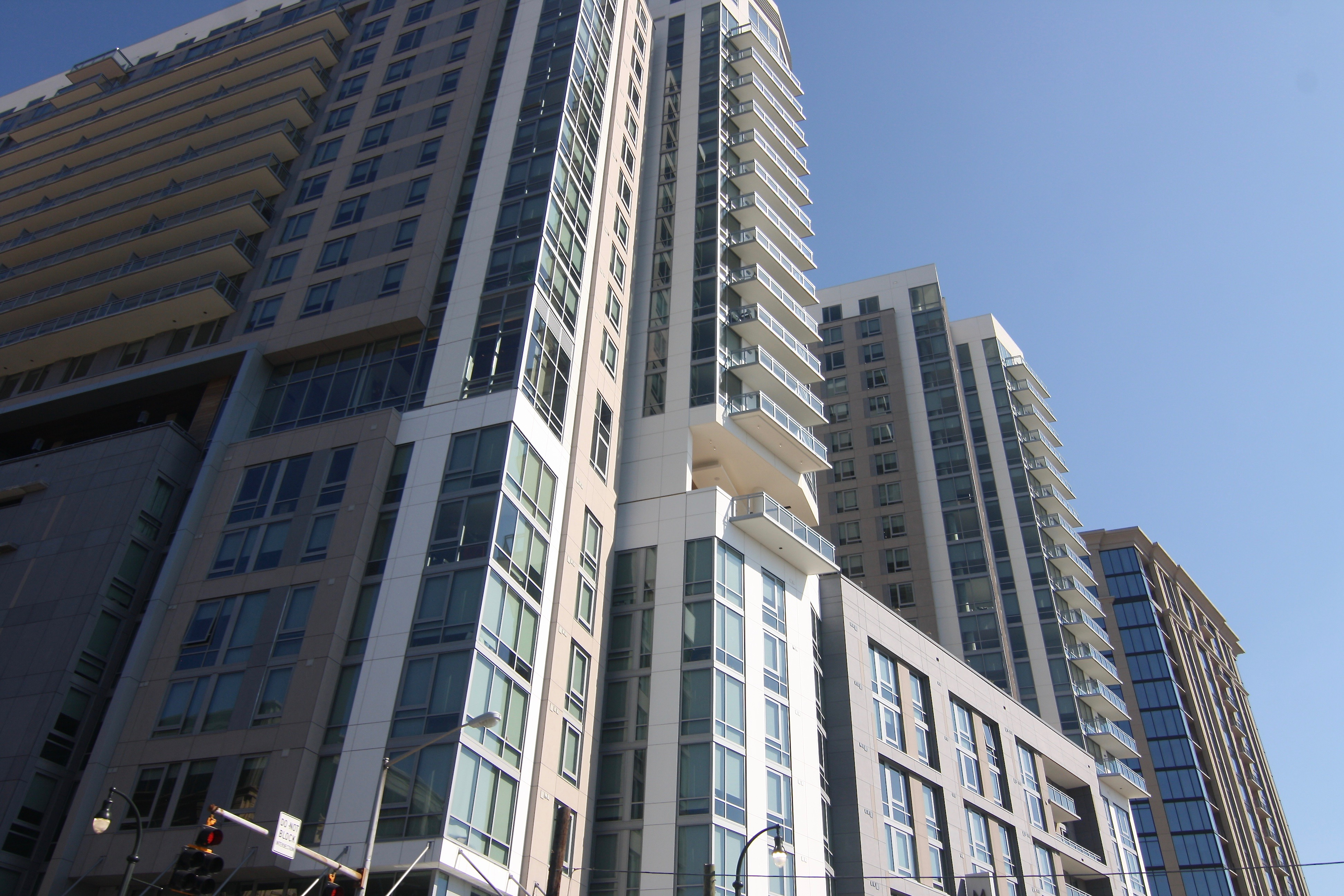 Two tower developments show in the sunshine, with balconies and many glassy windows.