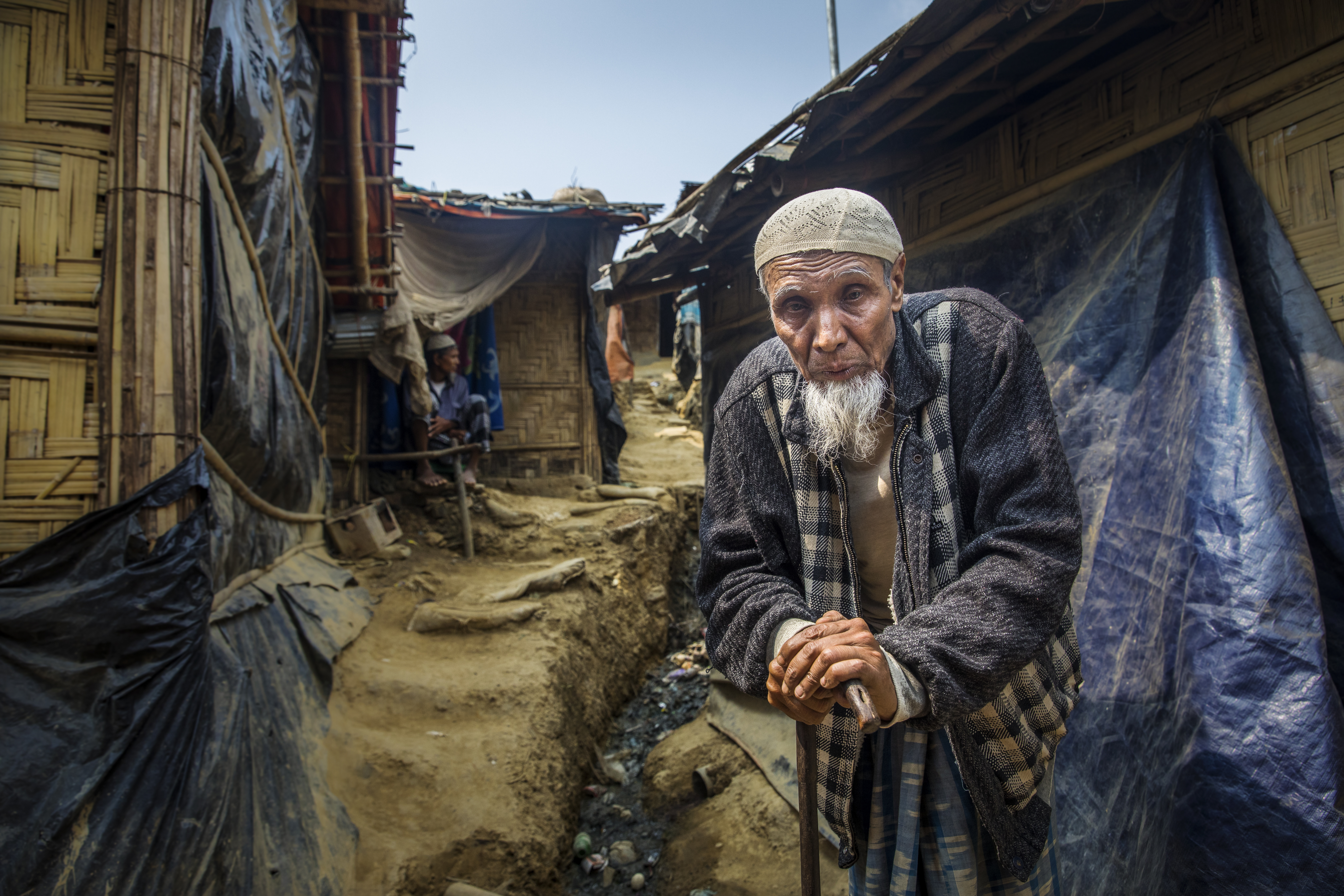 An elderly man leaning on a walking stick and standing in a narrow alley between two huts.