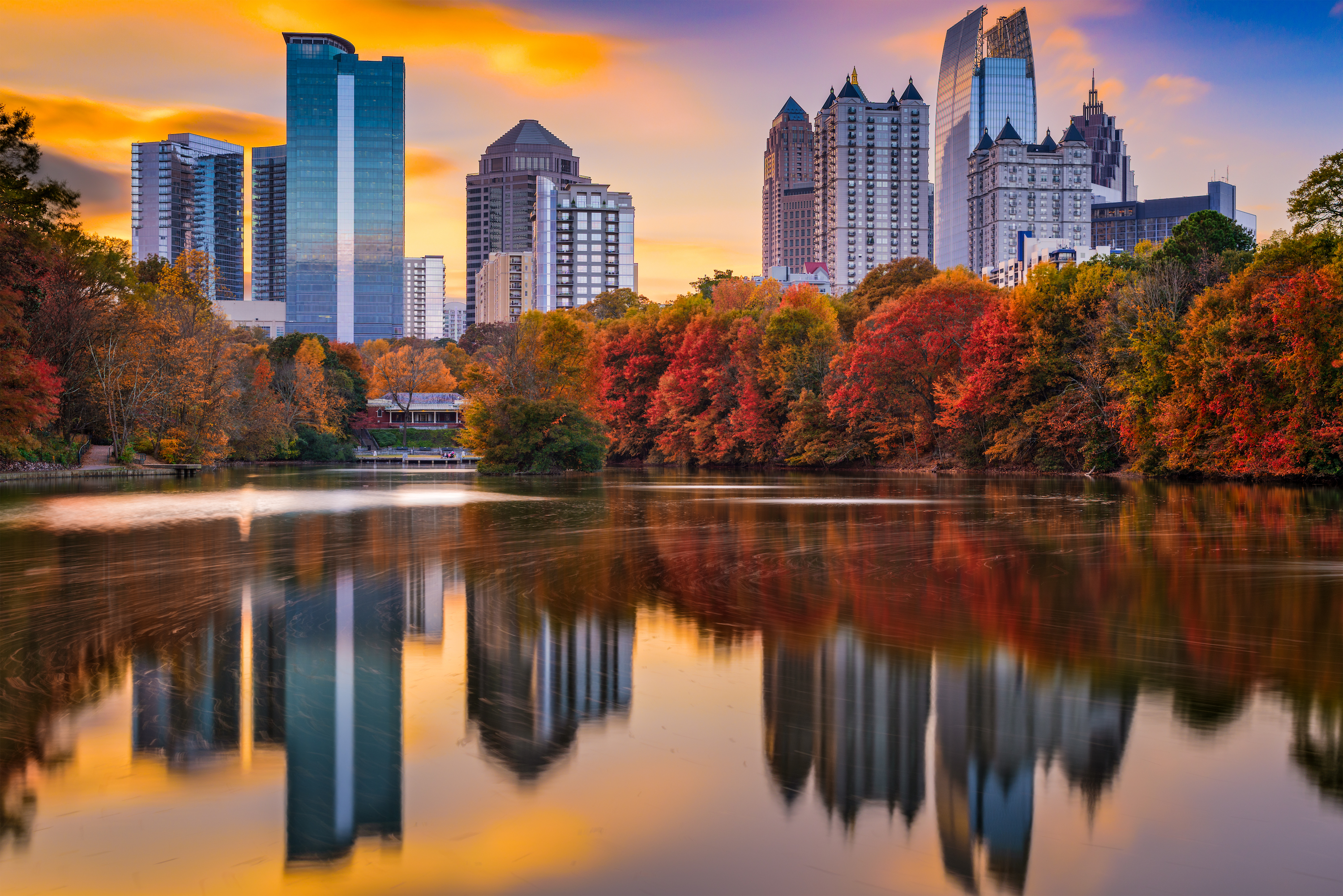 Red and orange trees sit adjacent to a calm river, with the skyscrapers from the Atlanta skyline in the background.