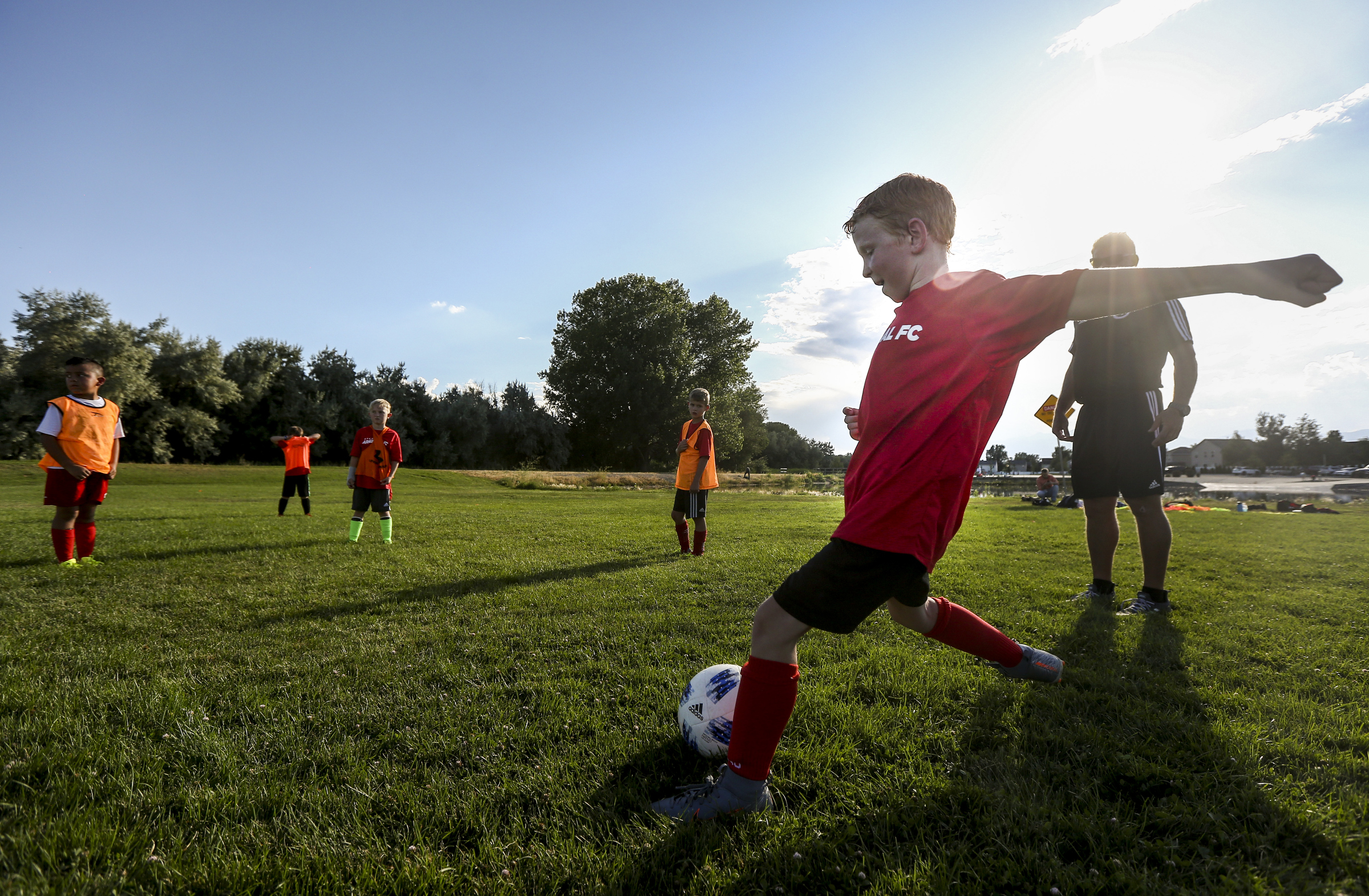 Jones Jackson, 9, kicks the ball to teammates during a keep-away drill in a practice at North Lake Park in Lehi on Thursday, Aug. 1, 2019.