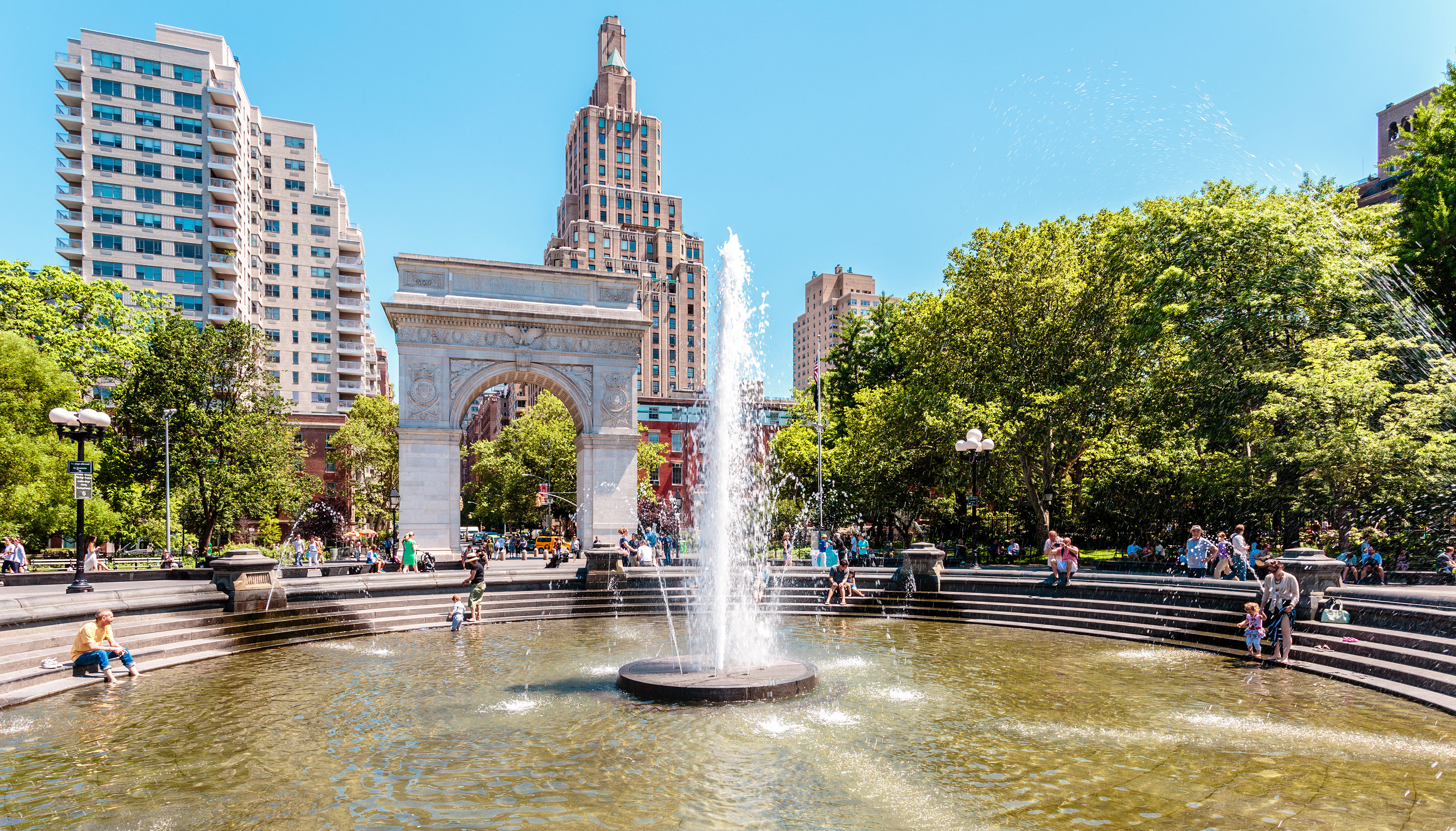 The Washington Square Park fountain is in the foreground. There are people sitting on the edge of the fountain. The Washington Square arch and city buildings are in the background.