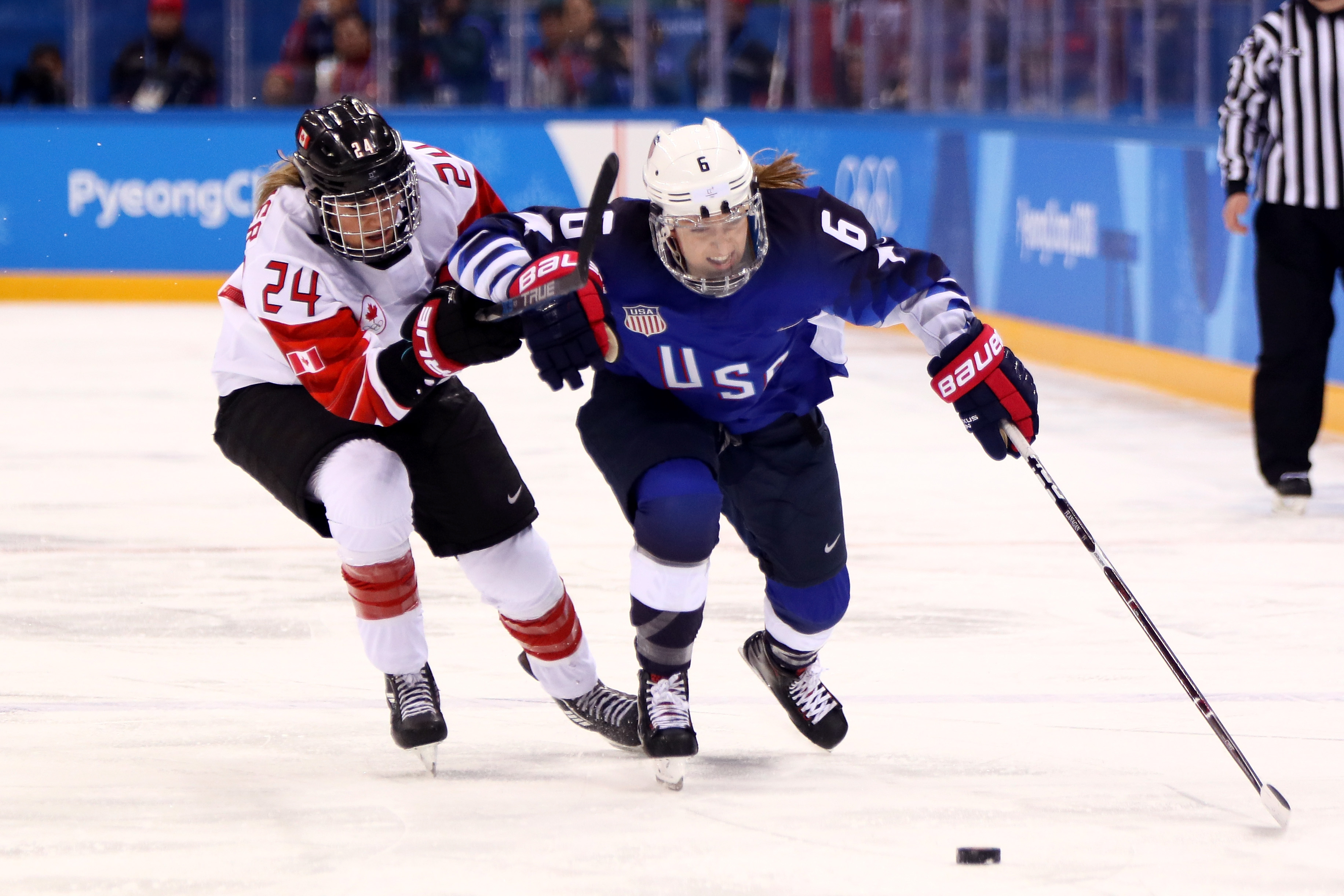 Kali Flanagan #6 of the United States controls the puck against Natalie Spooner #24 of Canada