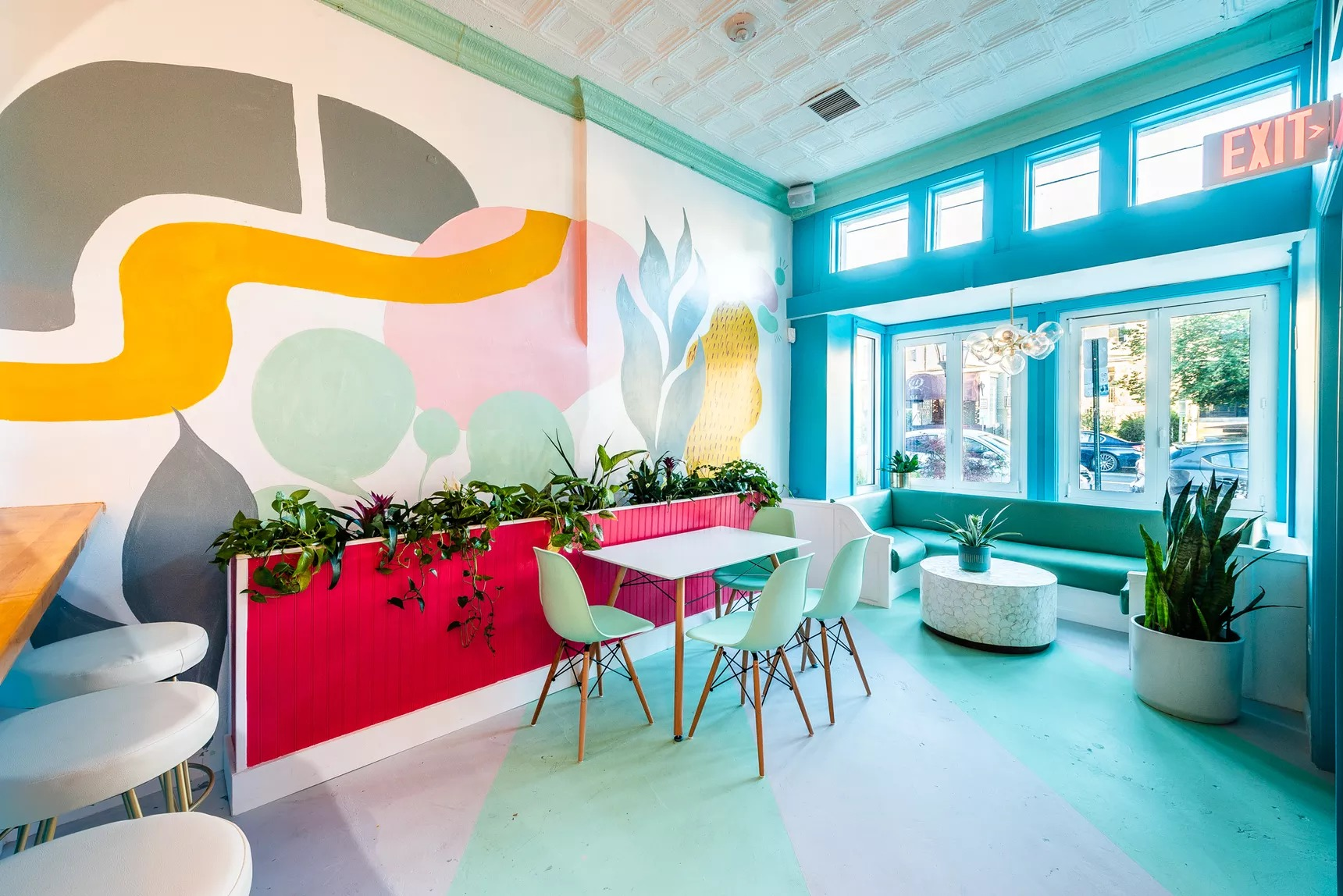 A dining room with a mural on one wall featuring gray shapes, a long yellow shape, a sea foam green circle, and a pink circle, plus stools along one wall and a table and chairs in the center