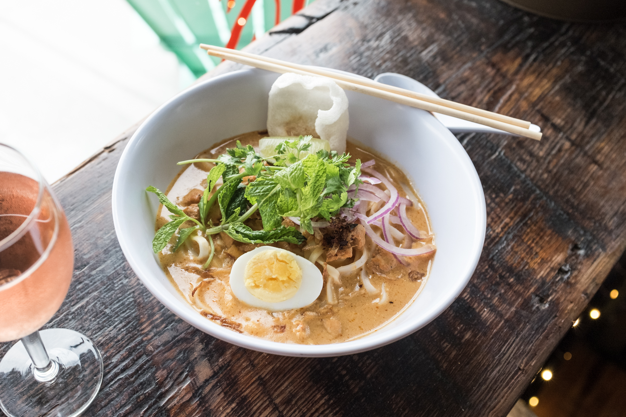 Chicken coconut noodles from Rangoon NoodleLab, an orange broth in a white bowl