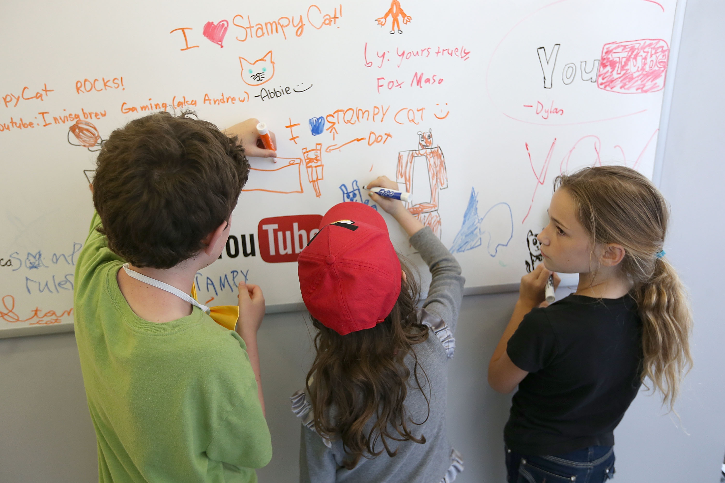 Three children draw on a whiteboard at a YourTube launch event.