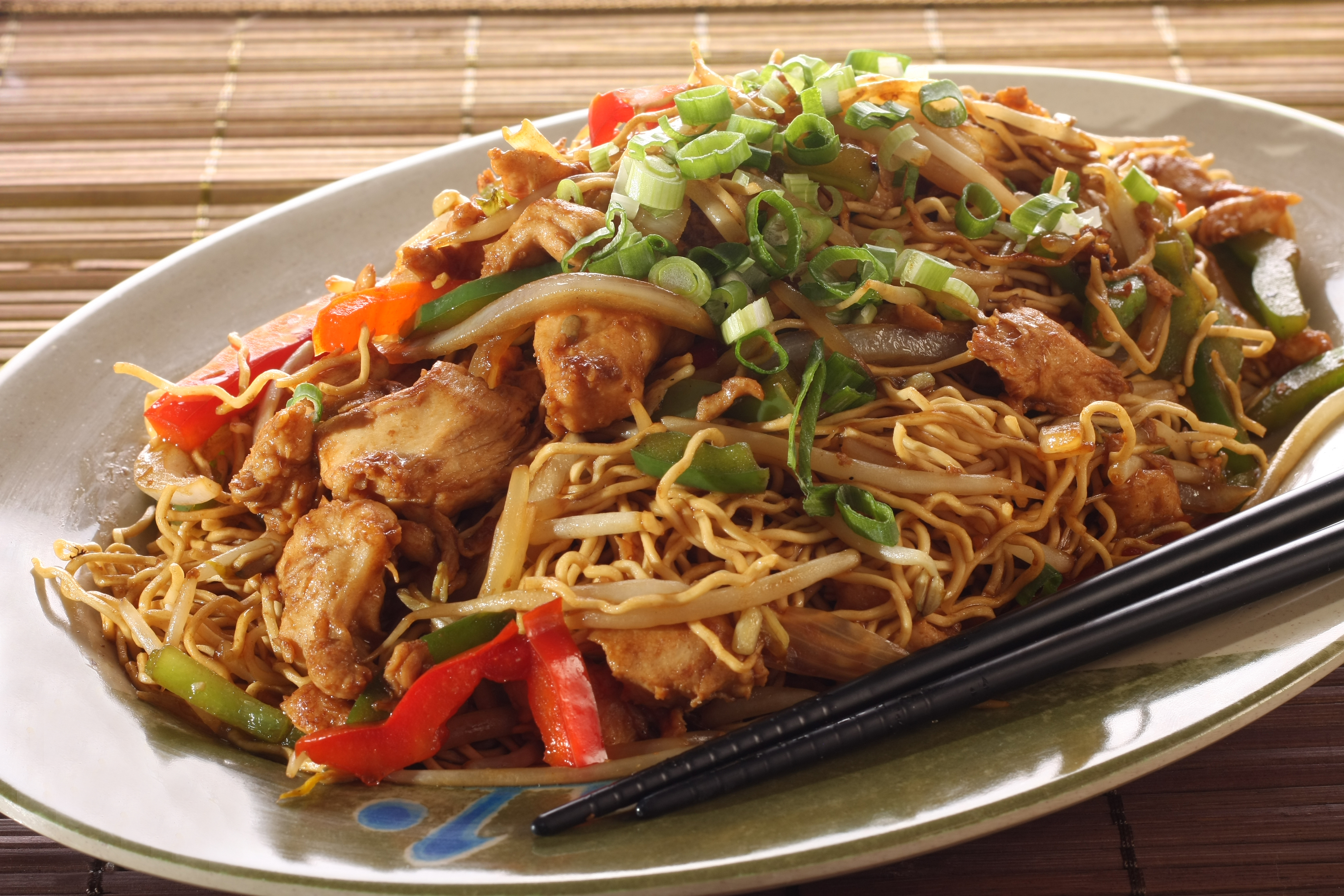 Chow mein on a gray plate with a set of black chopsticks