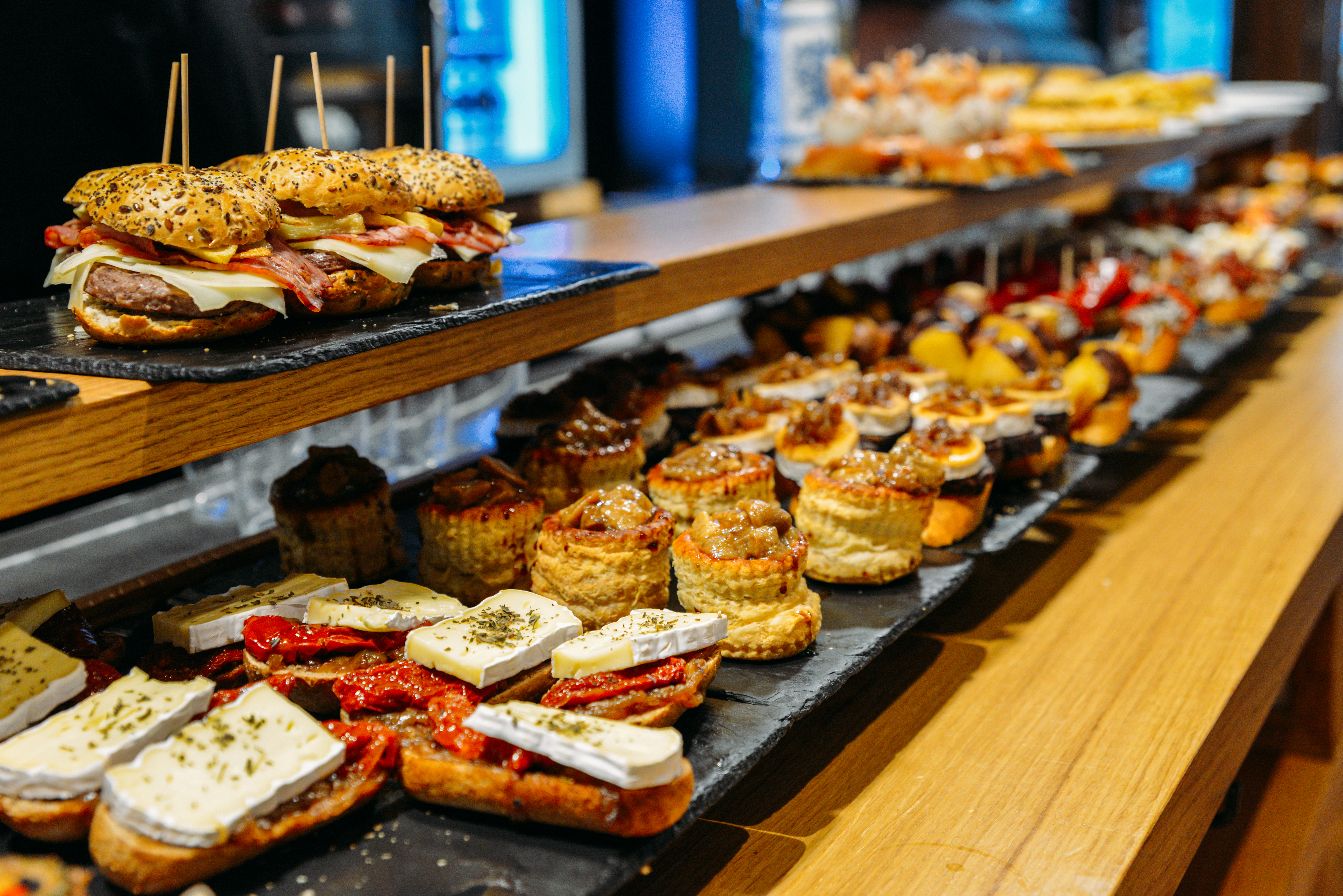 Pintxos piled on slate trays atop a wooden table