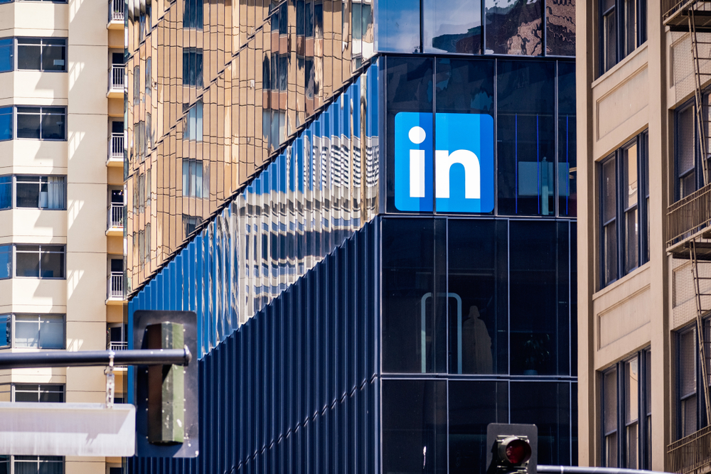 """The LinkedIn logo—a blue square with the word """"in"""" written in white""""—on the side of a high-rise building with a black glass facade."""