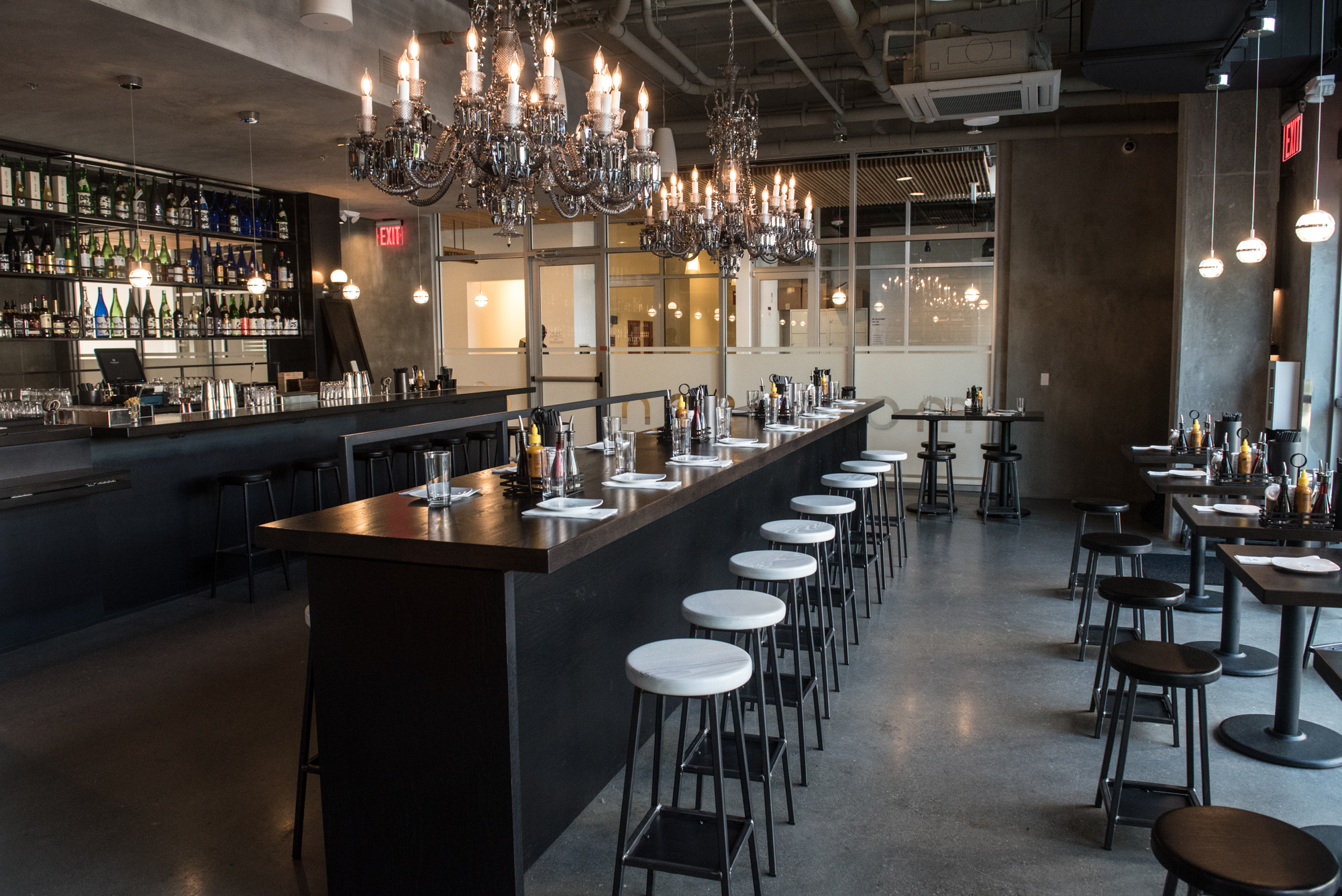 A view of the upper level at Momosan Seattle, with a long table for diners, silver chandeliers, and a bar to the left.
