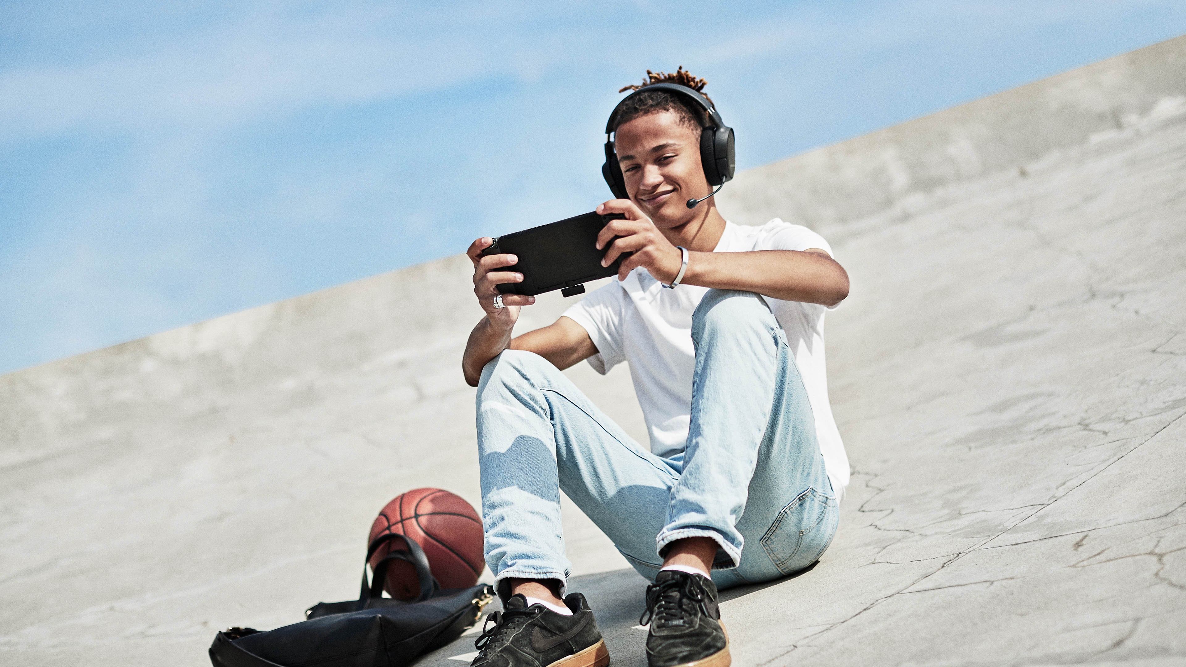 A teenager plays on a Nintendo Switch while sitting on a paved sidewalk wearing the Arctis 1 Wireless headset