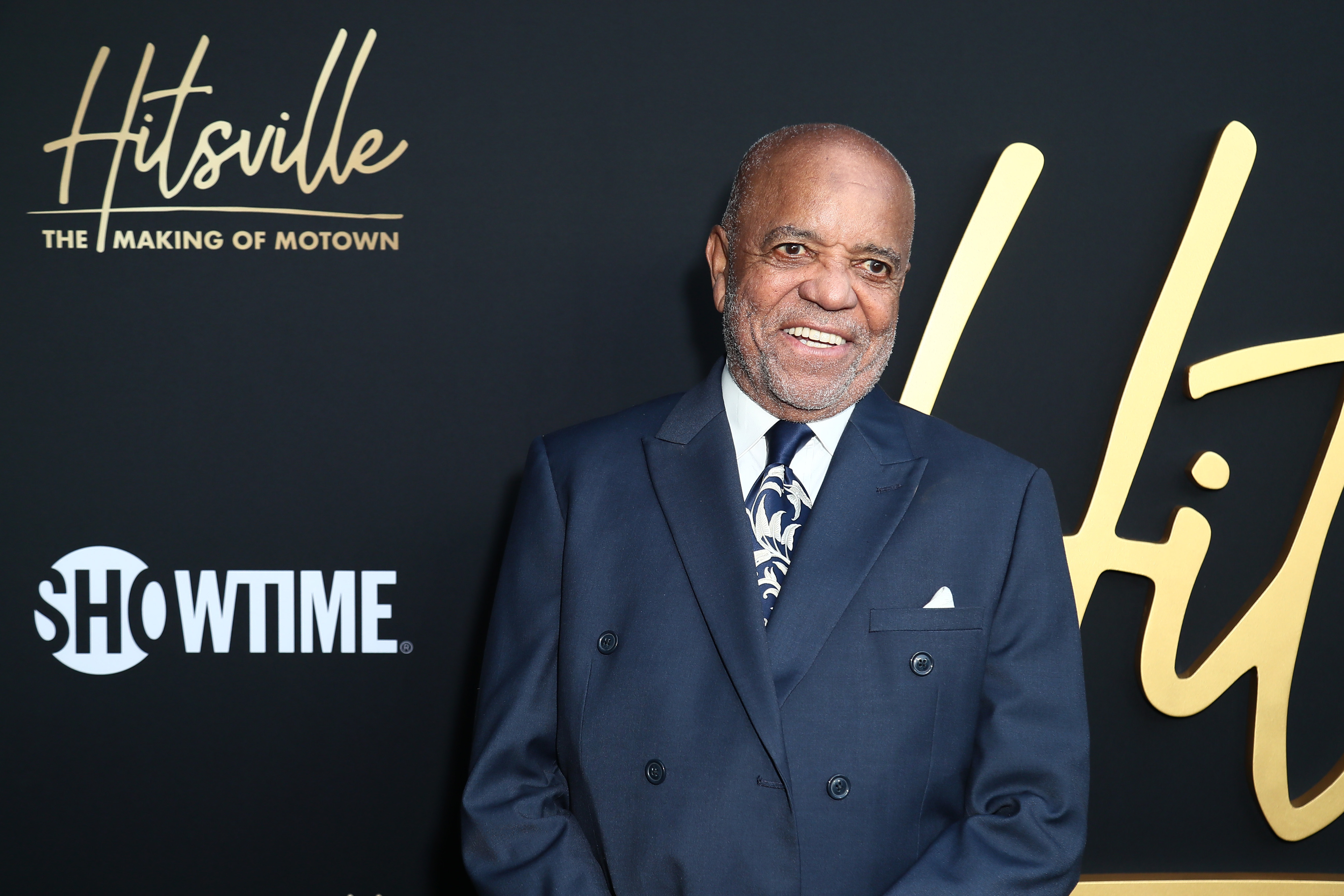 "Berry Gordy wearing a blue suit against a backdrop with ""Showtime"" and ""Hitsville: the Making of Motown."""