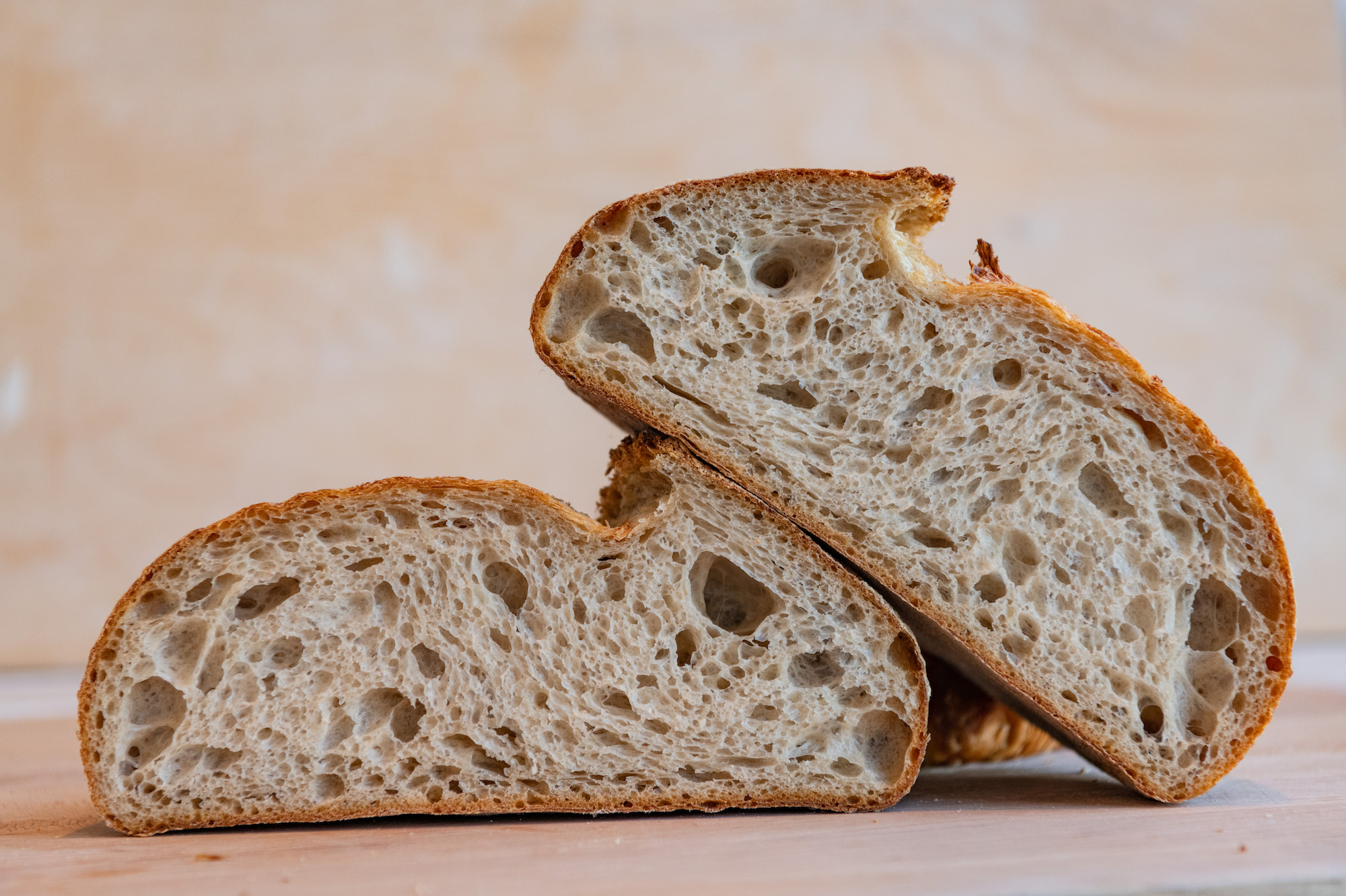 A loaf of rustic bread, cut in half to show the crumb.