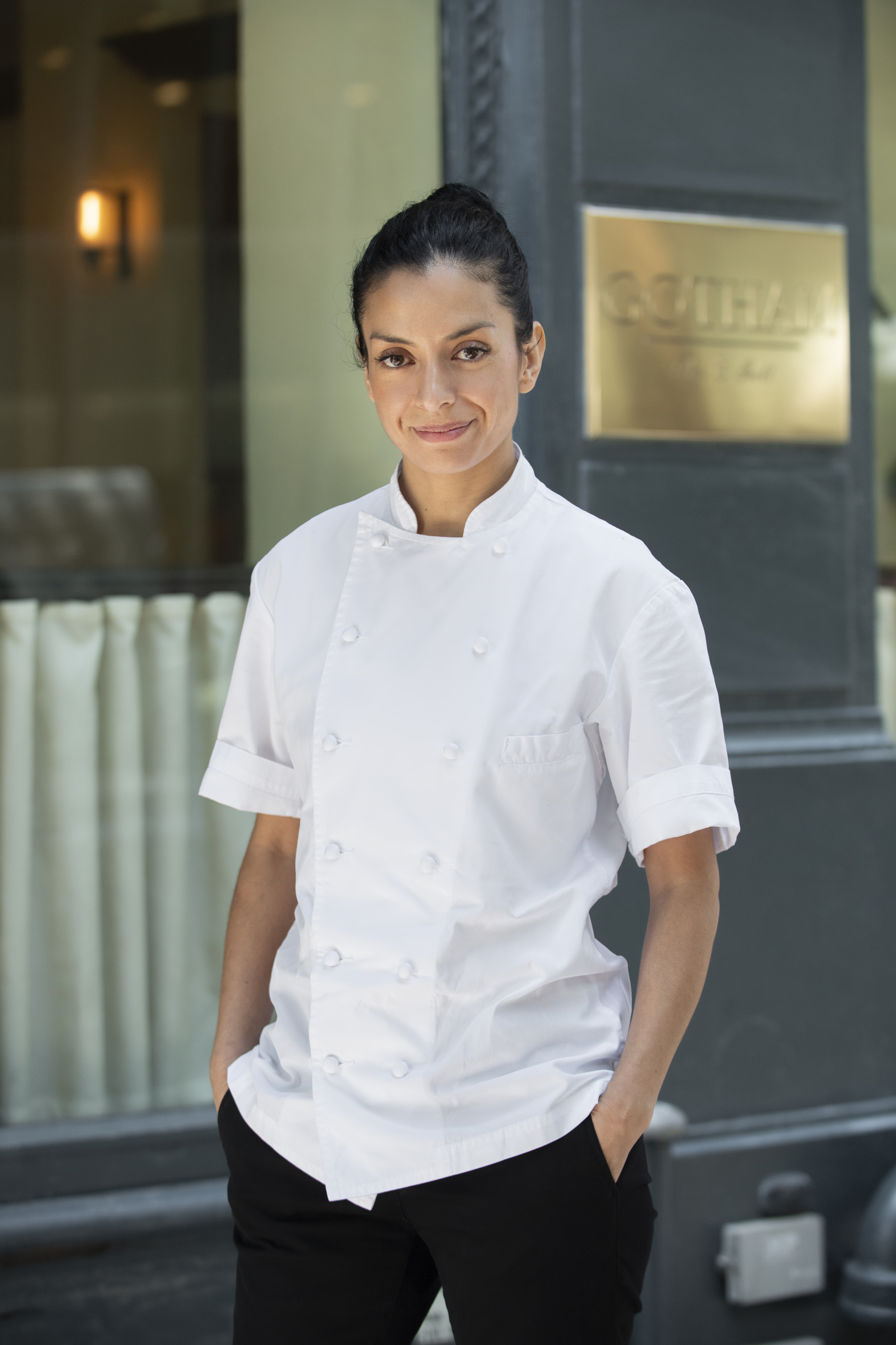 Victoria Blamey poses in a chef's jacket in front of Gotham Bar & Grill