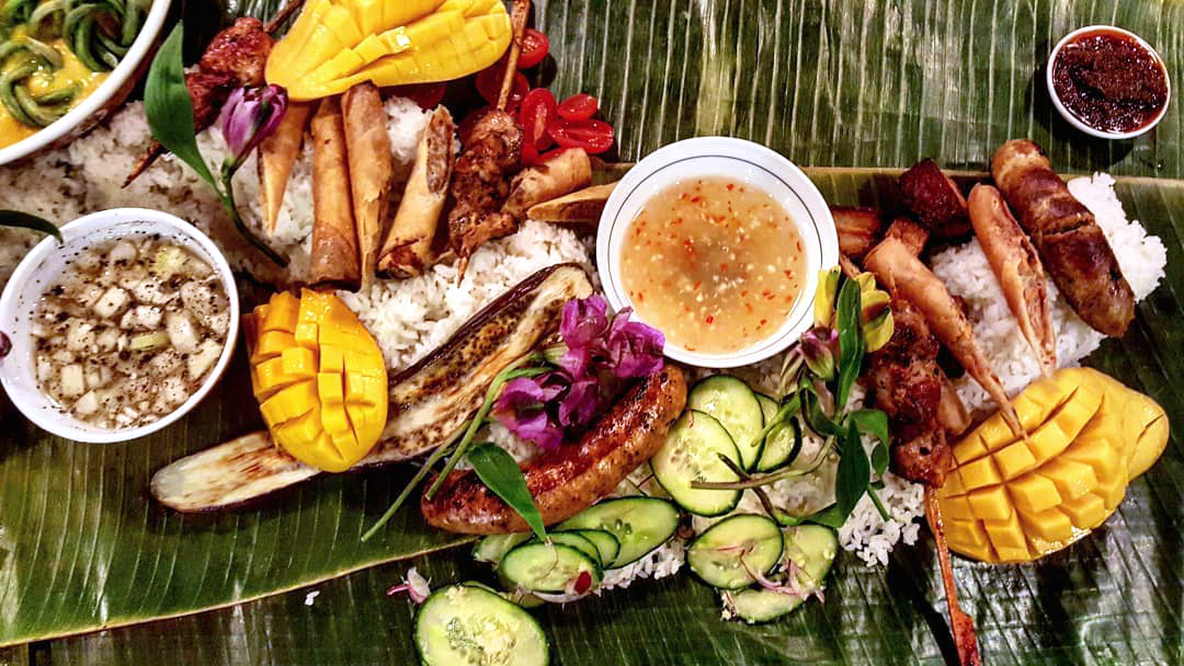 Cut mango, sliced cucumbers, sausages, and other meats form a spread atop banana leaves in a kamayan-style Filipino dinner.