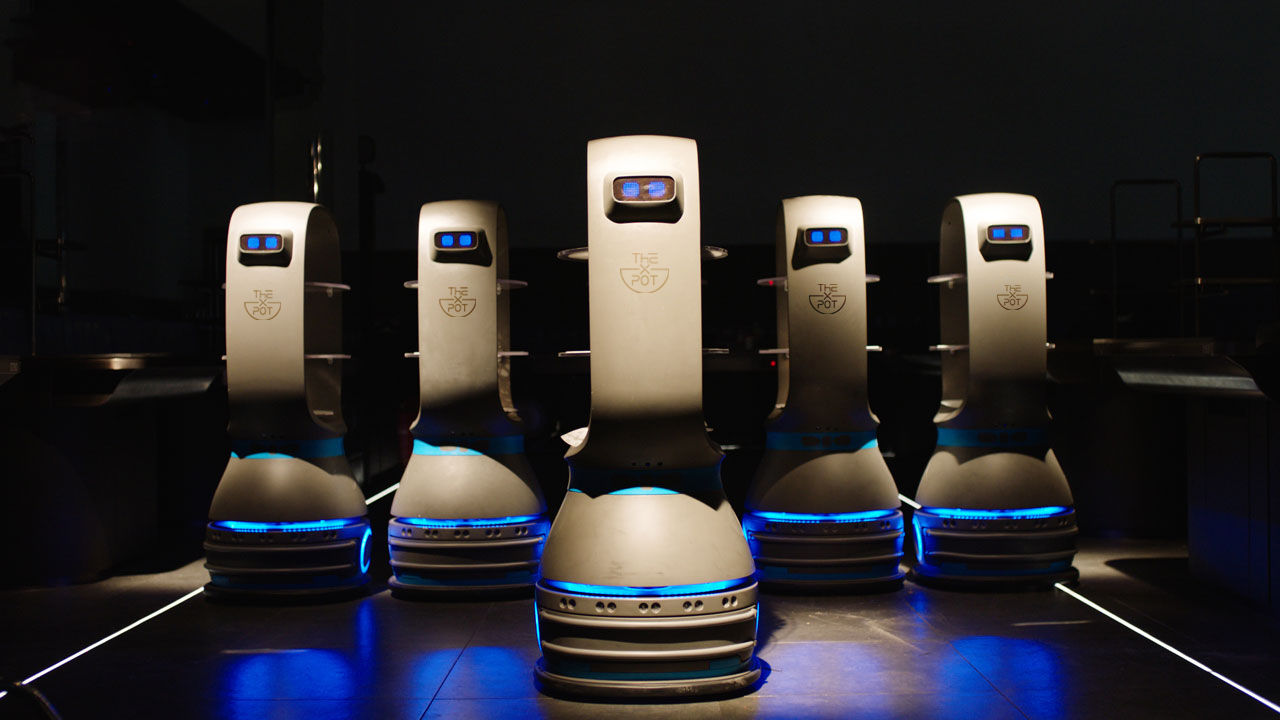 Five robots that will serve as food runners for X Pot in Chicago. They have blue eyes and are friendly.