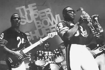 """From left: Running back Dennis Gentry on bass, guard Stefan Humphries on drums and running back Calvin Thomas on saxophone during the music video for """"The Super Bowl Shuffle."""""""